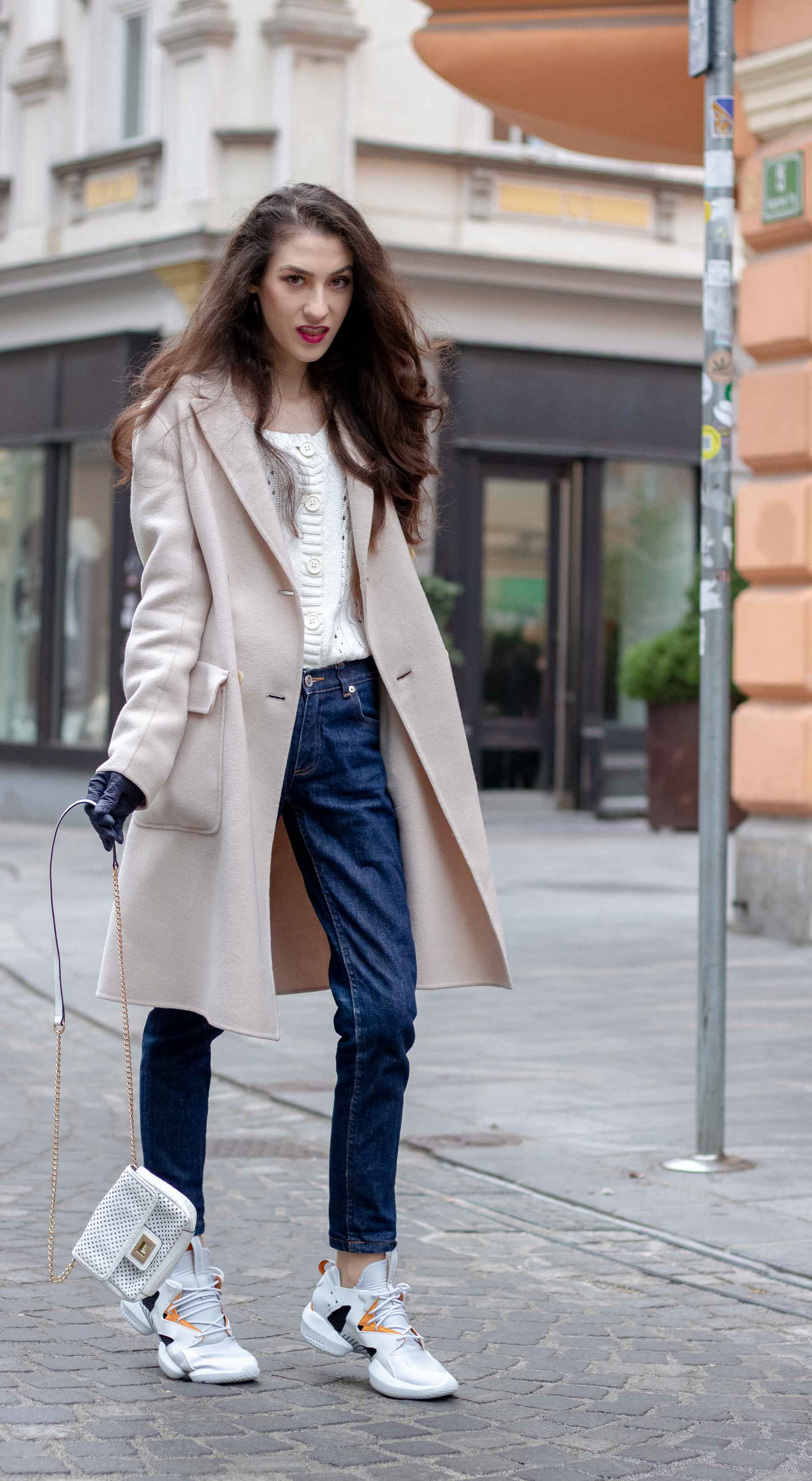 Beautiful Slovenian Fashion Blogger Veronika Lipar of Brunette from Wall wearing white Mango cardigan tucked into dark blue denim jeans from a.p.c., Weekend Max Mara coat, Reebok instapump sneakers walking on the street