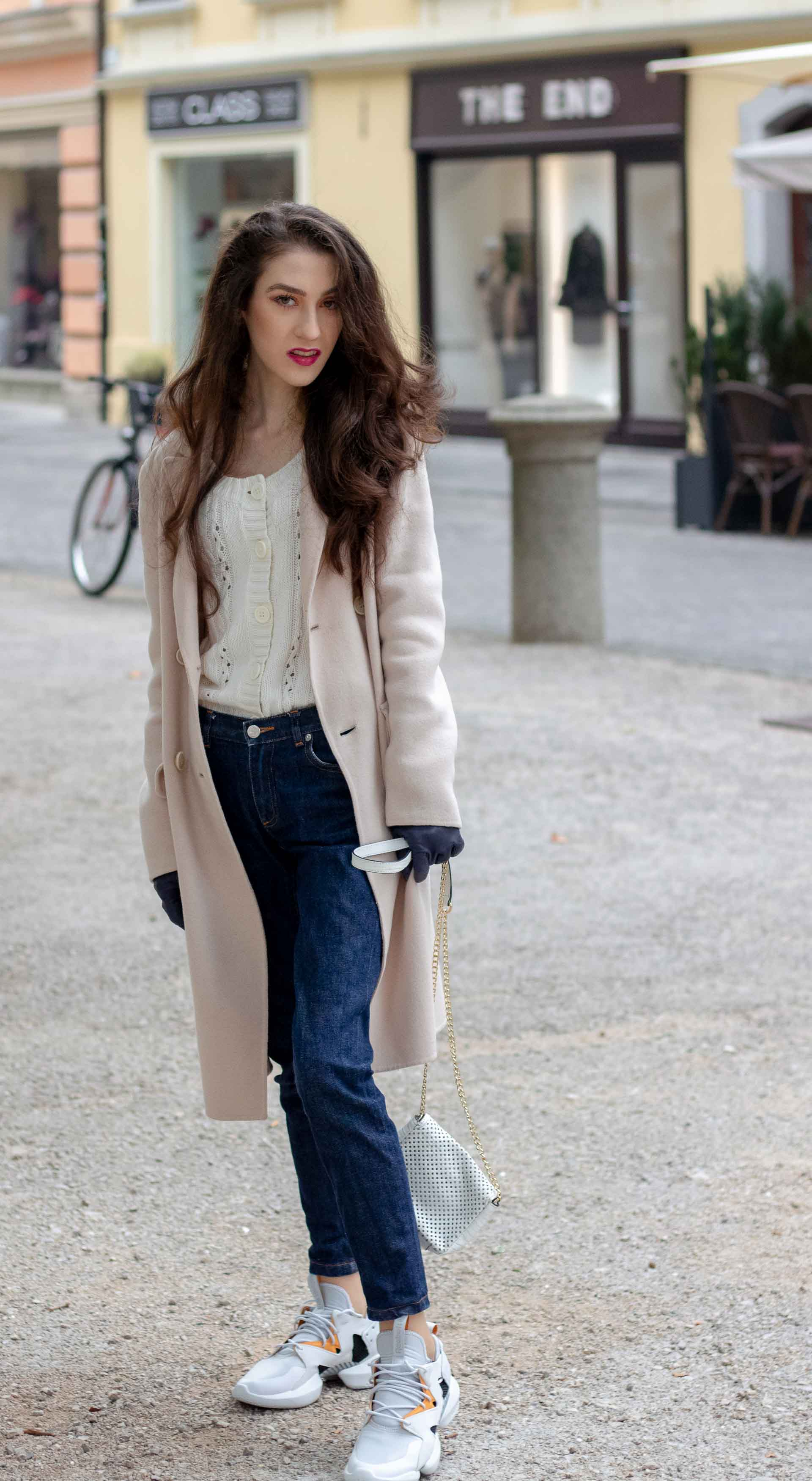 Beautiful Slovenian Fashion Blogger Veronika Lipar of Brunette from Wall wearing white Mango cardigan tucked into dark blue denim jeans from a.p.c., Weekend Max Mara coat, Reebok instapump sneakers in autumn