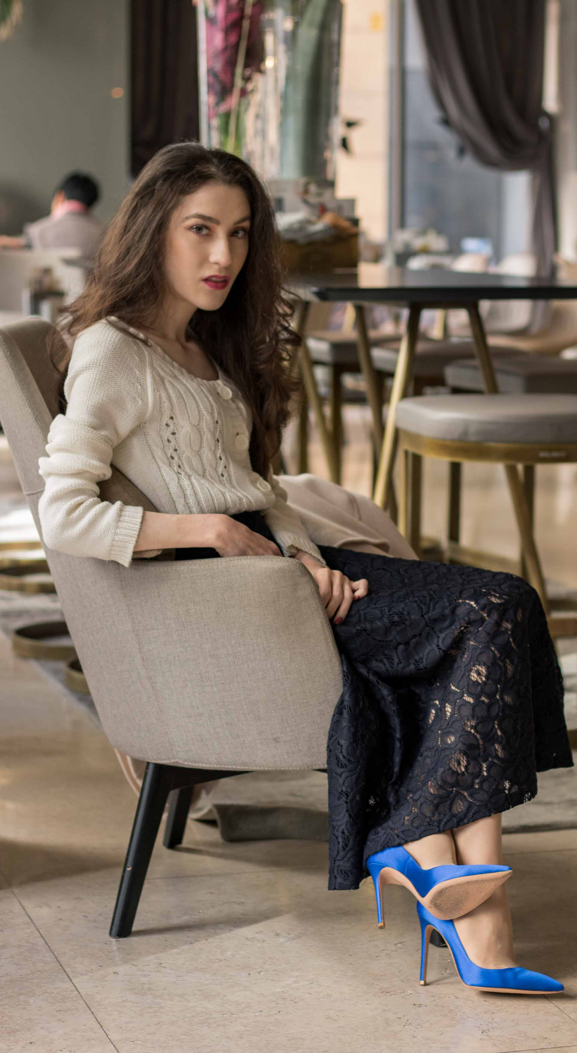 Beautiful Slovenian Fashion Blogger Veronika Lipar of Brunette from Wall wearing white Mango cardigan etude into black lace midi skirt, blue Gianvito Rossi pumps for fall Sunday brunch sitting on the armchair