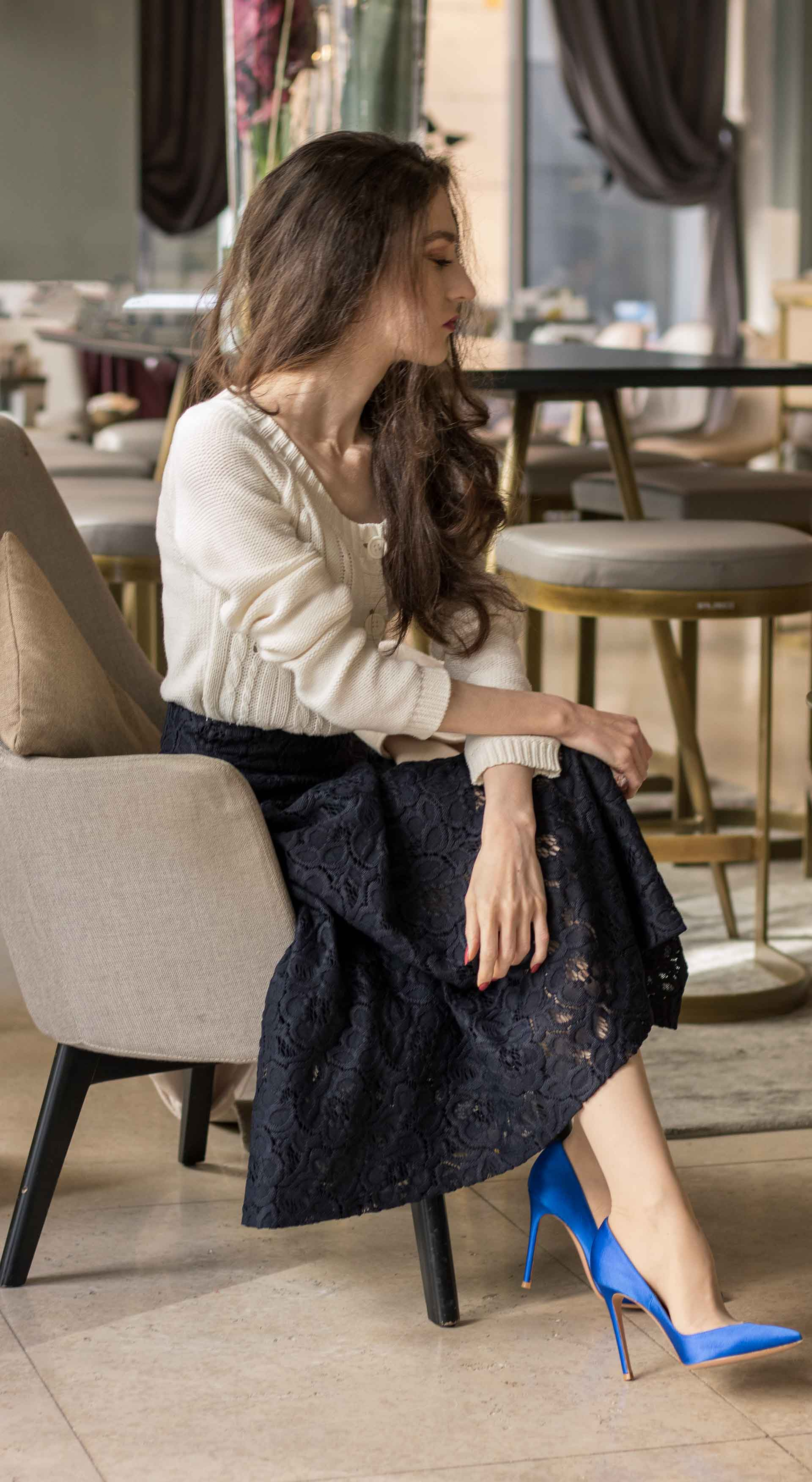Beautiful Slovenian Fashion Blogger Veronika Lipar of Brunette from Wall dressed in white Mango cardigan etude into black lace midi skirt, blue Gianvito Rossi pumps for fall Sunday brunch sitting on the armchair