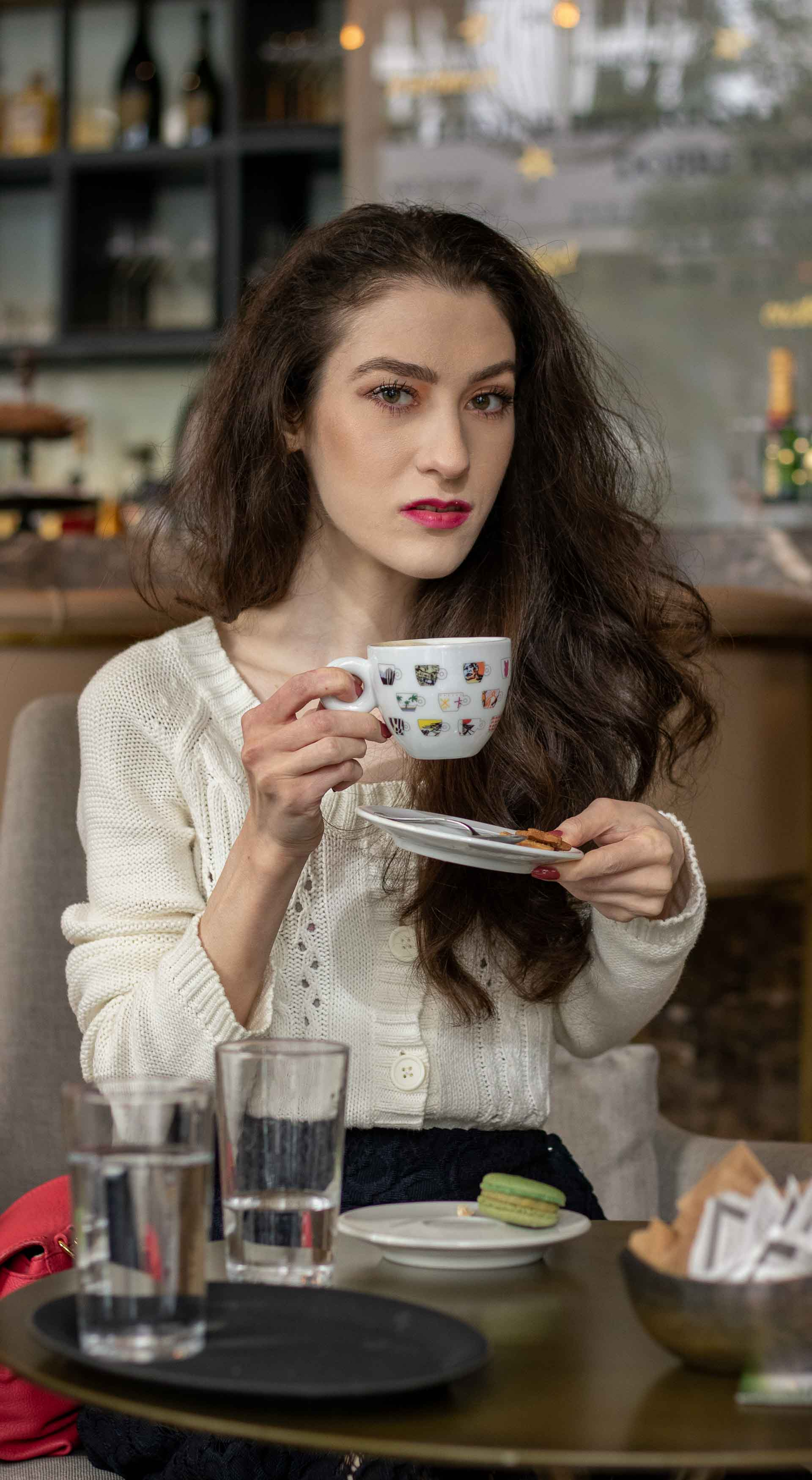 Beautiful Slovenian Fashion Blogger Veronika Lipar of Brunette from Wall wearing white Mango cardigan etude into black lace midi skirt, blue Gianvito Rossi pumps for fall Sunday brunch holding coffee cup