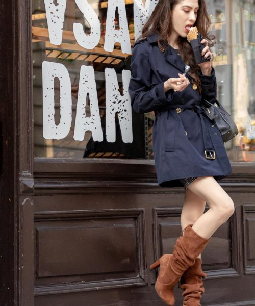 Beautiful Slovenian Fashion Blogger Veronika Lipar of Brunette from Wall dressed in Stuart Weitzman brown slouchy boots, blue Michael Kors trench coat, black top handle bag while eating ice cream in fall on the street