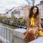 Beautiful Slovenian Fashion Blogger Veronika Lipar of Brunette from Wall dressed in Escada camel wrap coat, Escada yellow dress, Stuart Weitzman brown over the knee boots, Escada yellow shoulder bag for a day date in fall