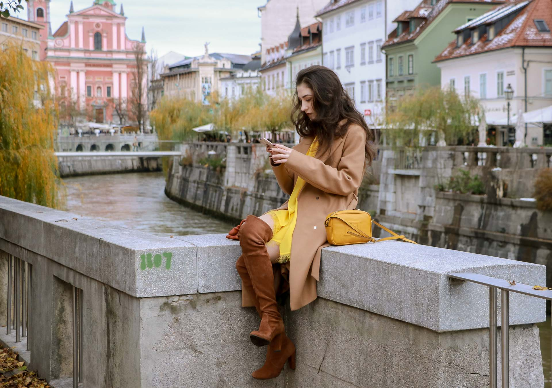 Beautiful Slovenian Fashion Blogger Veronika Lipar of Brunette from Wall dressed in Escada camel wrap coat, Escada yellow dress, Stuart Weitzman brown over the knee boots, Escada yellow shoulder bag sitting above the river