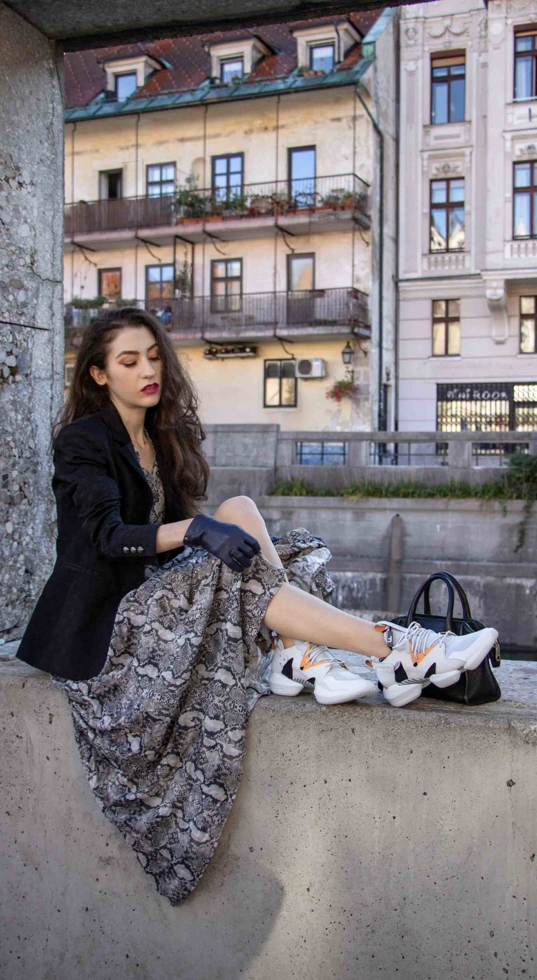 Beautiful Slovenian Fashion Blogger Veronika Lipar of Brunette from Wall dressed in Zara snakeskin print dress with black boyfriend blazer, Reebok instapump chunky sneakers, blue gloves, black top handle bag sitting on the wall in Ljubljana in autumn