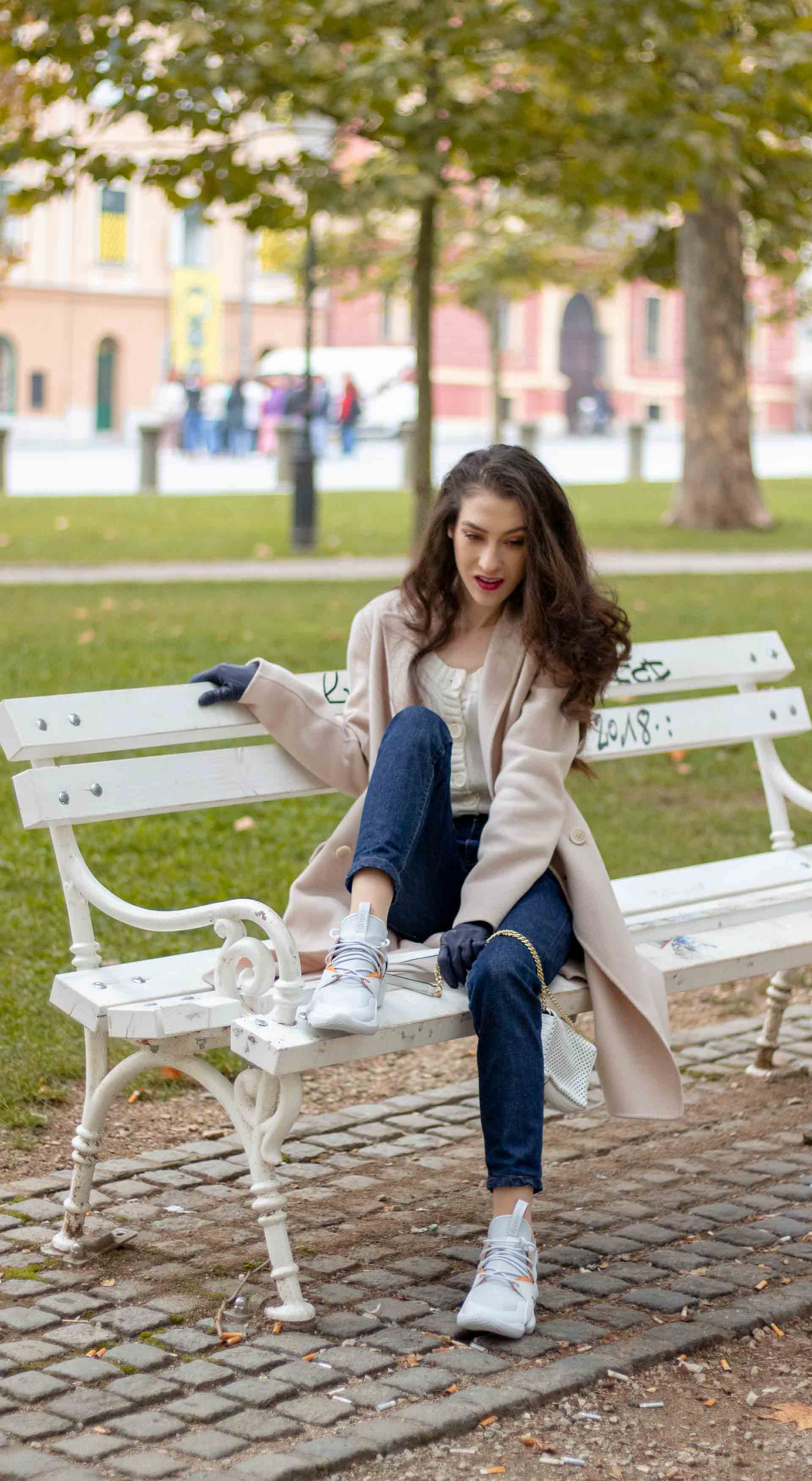 Beautiful Slovenian Fashion Blogger Veronika Lipar of Brunette from Wall wearing white Mango cardigan tucked into dark blue denim jeans from a.p.c., Weekend Max Mara coat, Reebok instapump sneakers in fall