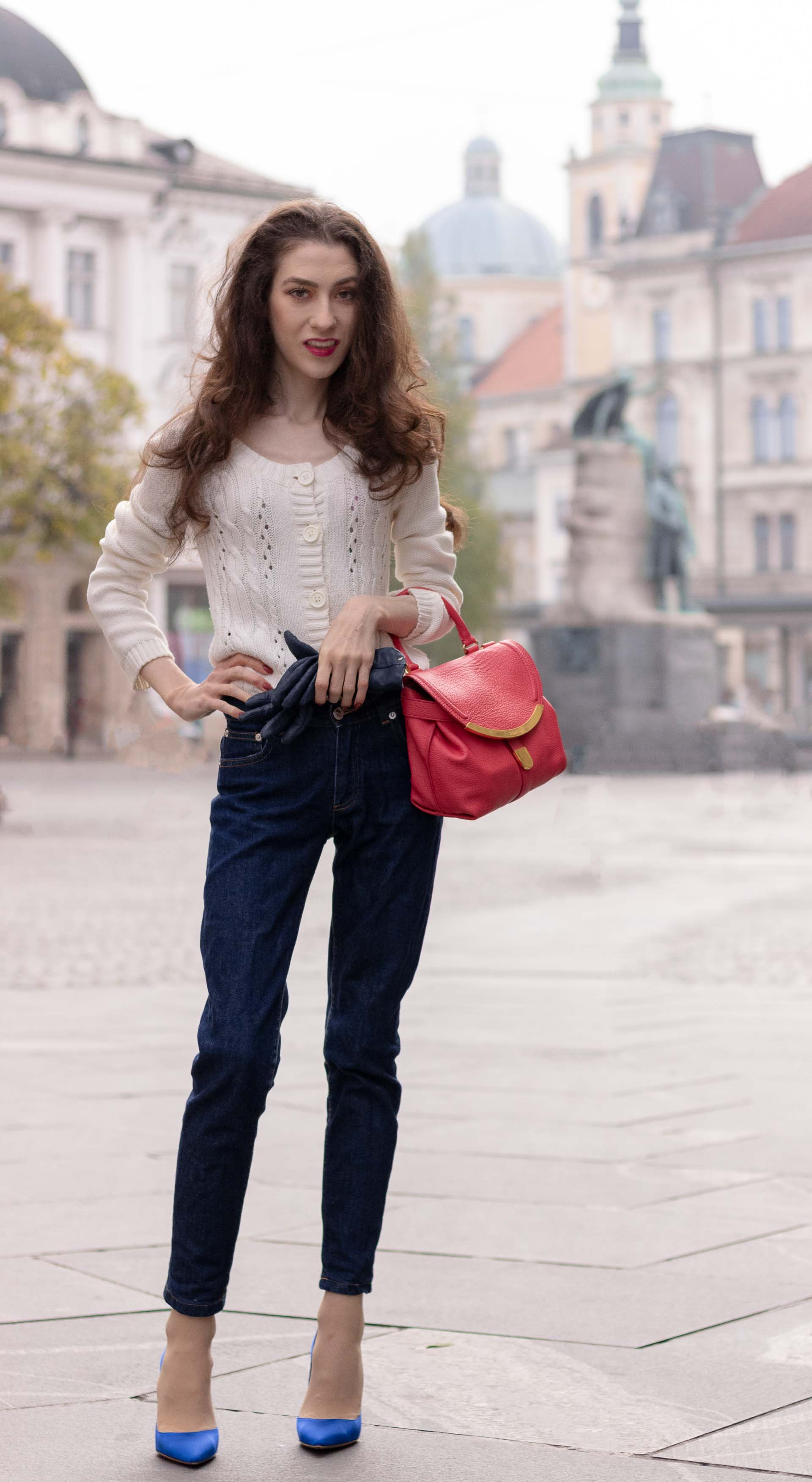 Beautiful Slovenian Fashion Blogger Veronika Lipar of Brunette from Wall dressed in white Mango cardigan tucked into dark blue denim jeans from a.p.c., blue Gianvito Rossi pumps, pink top handle bag standing on the street