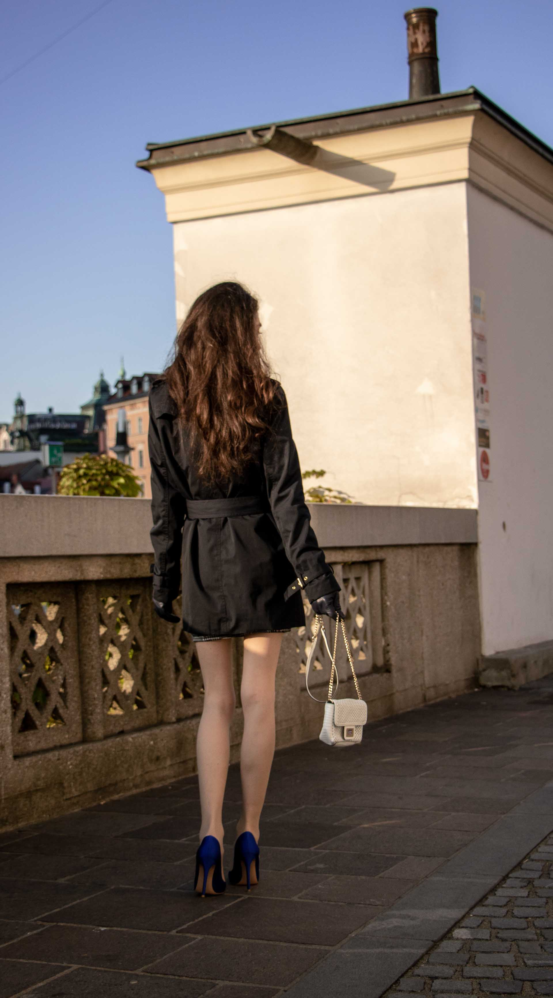 Beautiful Slovenian Fashion Blogger Veronika Lipar of Brunette from Wall wearing dark navy Michael Kors short trench coat, Gianvito Rossi blue satin court shoes, white chain shoulder bag walking home after clubbing in the morning