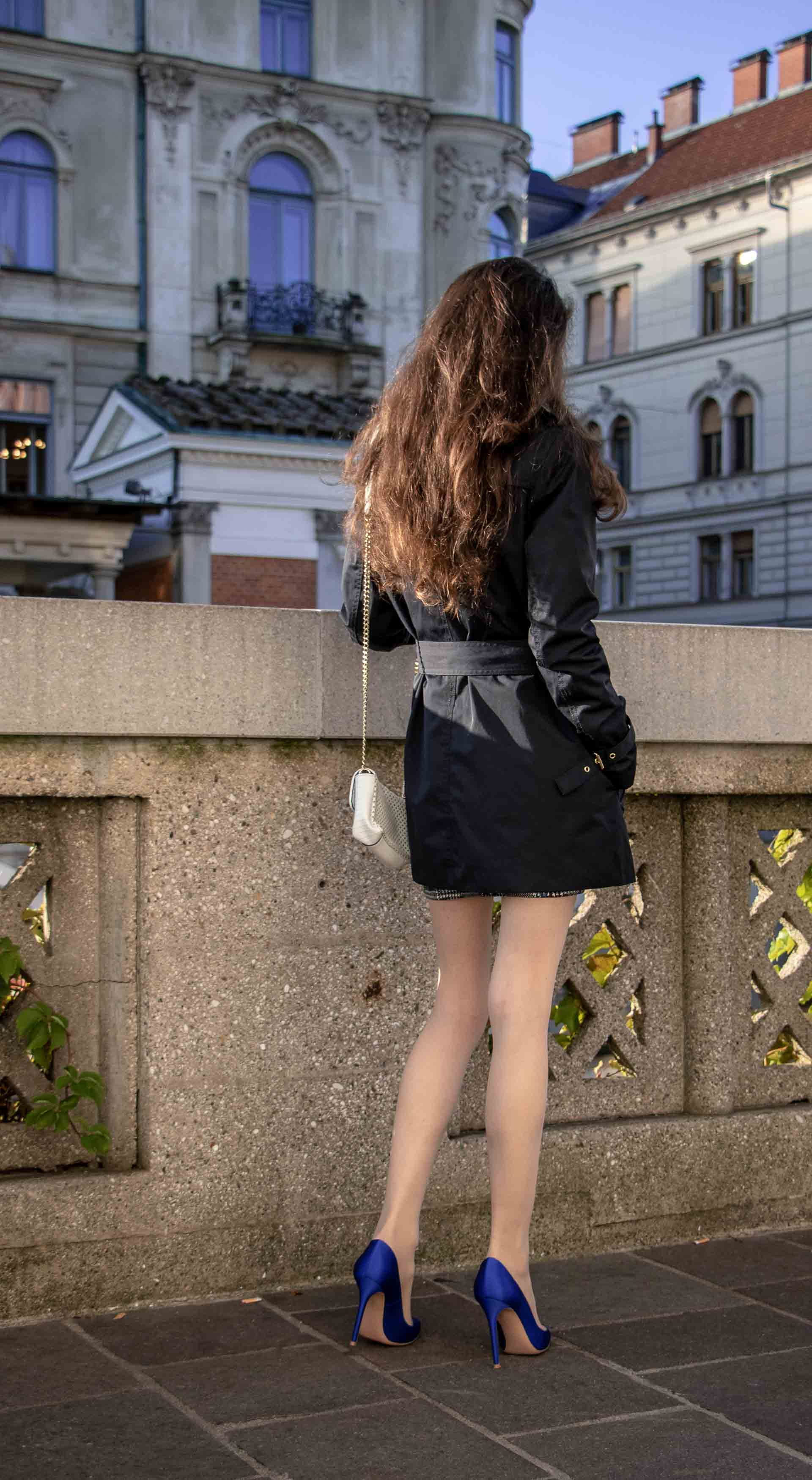Beautiful Slovenian Fashion Blogger Veronika Lipar of Brunette from Wall dressed in dark navy Michael Kors short trench coat, Gianvito Rossi blue satin court shoes, white chain shoulder bag walking home after partying