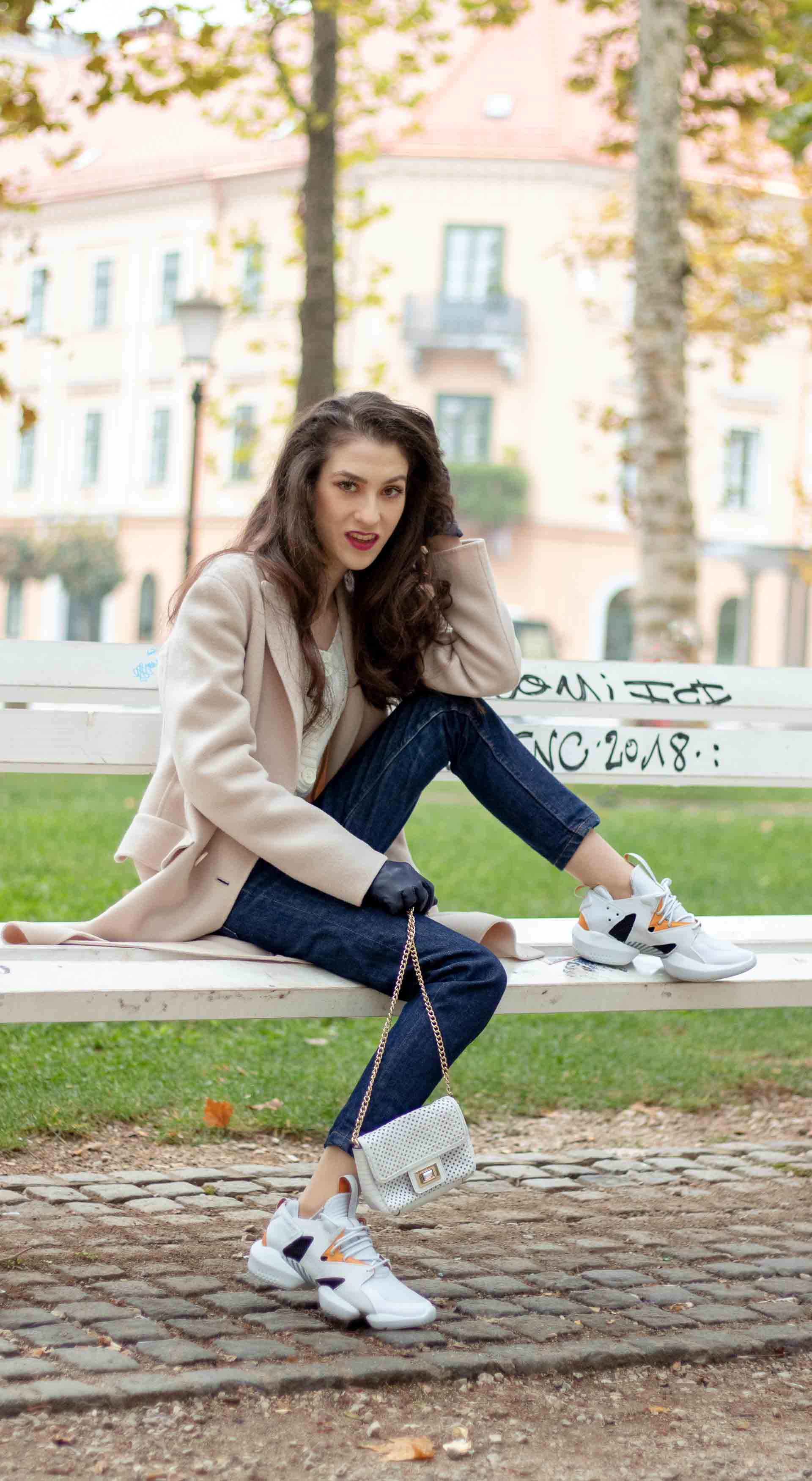 Beautiful Slovenian Fashion Blogger Veronika Lipar of Brunette from Wall dressed in white Mango cardigan tucked into A.P.C. dark blue denim jeans, Weekend Max Mara coat, Reebok instapump sitting on bench