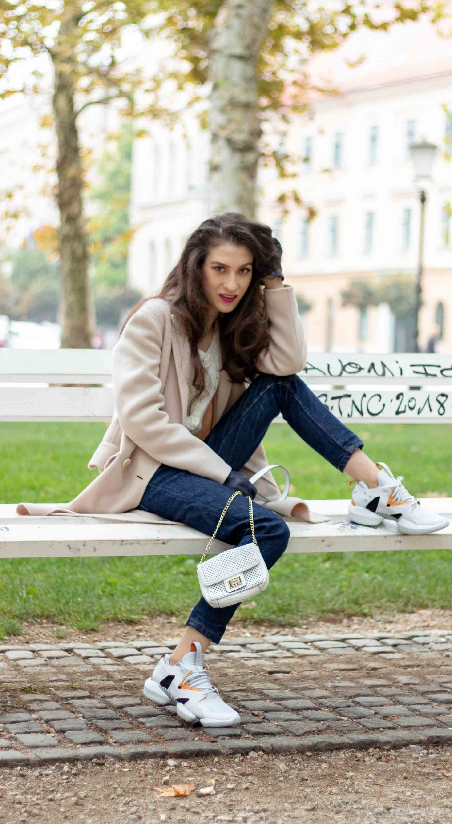 Beautiful Slovenian Fashion Blogger Veronika Lipar of Brunette from Wall wearing white Mango cardigan tucked into dark blue denim jeans from a.p.c., Weekend Max Mara coat, Reebok instapump sneakers sitting on the bench