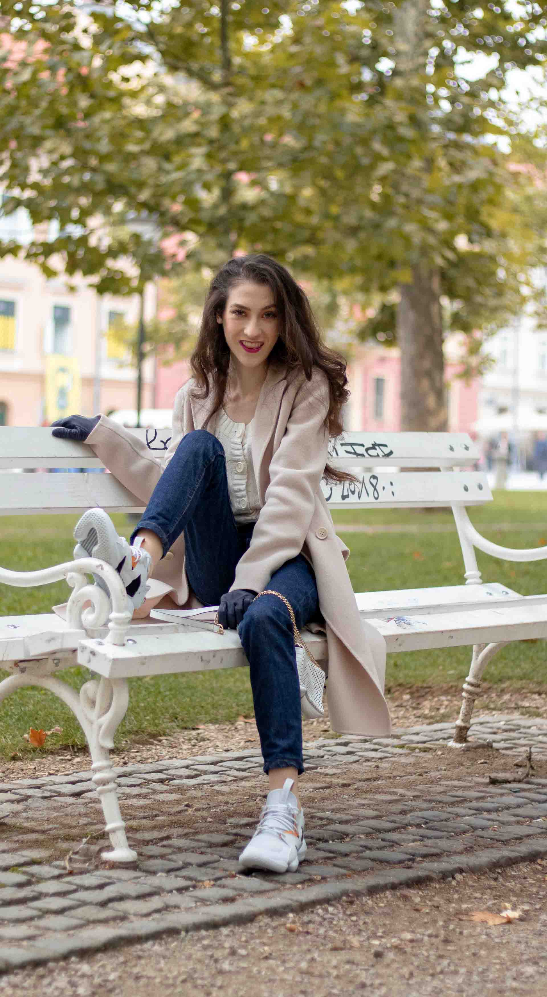 Beautiful Slovenian Fashion Blogger Veronika Lipar of Brunette from Wall dressed in white Mango cardigan tucked into A.P.C. dark blue denim jeans, Weekend Max Mara coat, Reebok instapump sitting on bench in park Zvezda