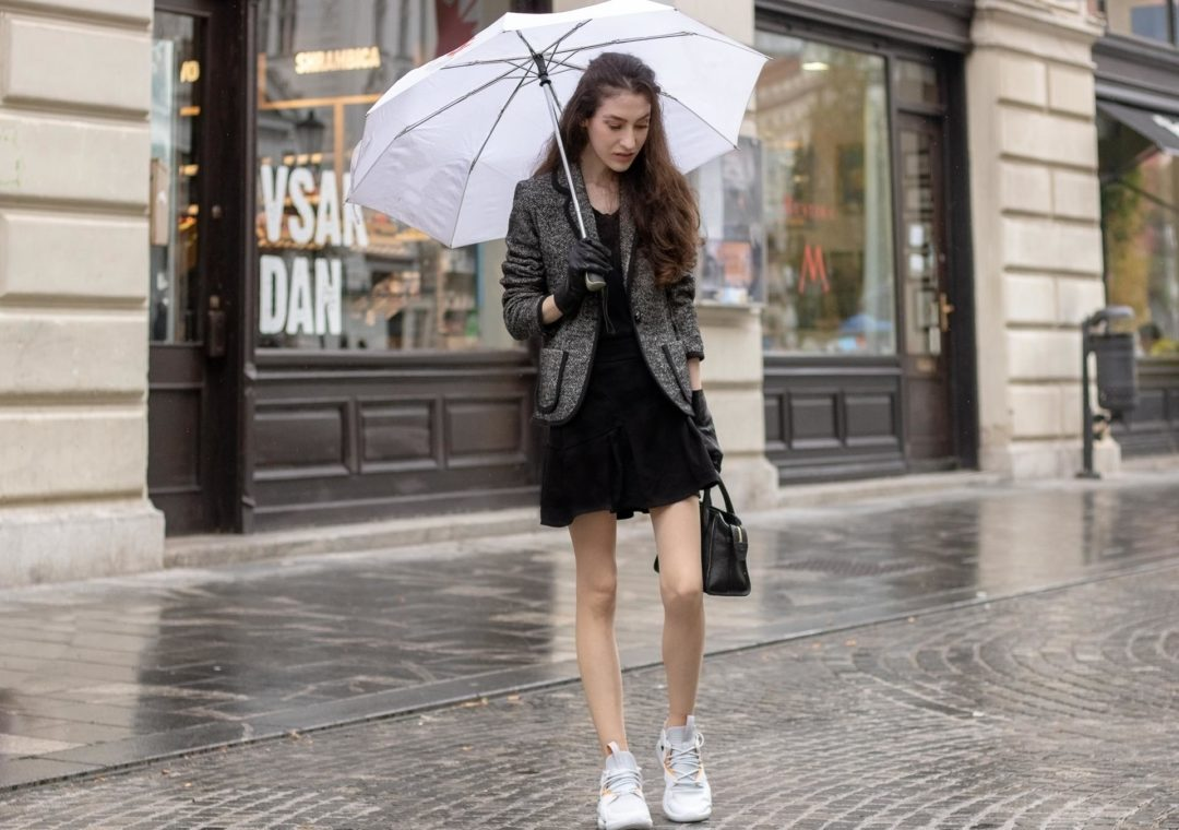 Beautiful Slovenian Fashion Blogger Veronika Lipar of Brunette from Wall dressed in Marella tweed jacket, black mini flare skirt, black sweatshirt Reebok instapump sneakers, black top handle bag, Burberry gloves, holding umbrella