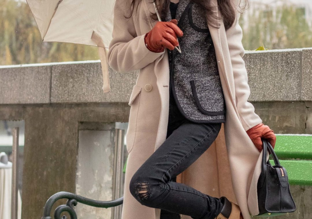 Most read Slovenian Fashion Blogger Veronika Lipar of Brunette from Wall Street wearing Diesel black skinny jeans with camel See By Chloé hiking boots, Weekend Max Mara double-breasted wool coat, black top handle bag, holding umbrella in the rain snow in Ljubljana