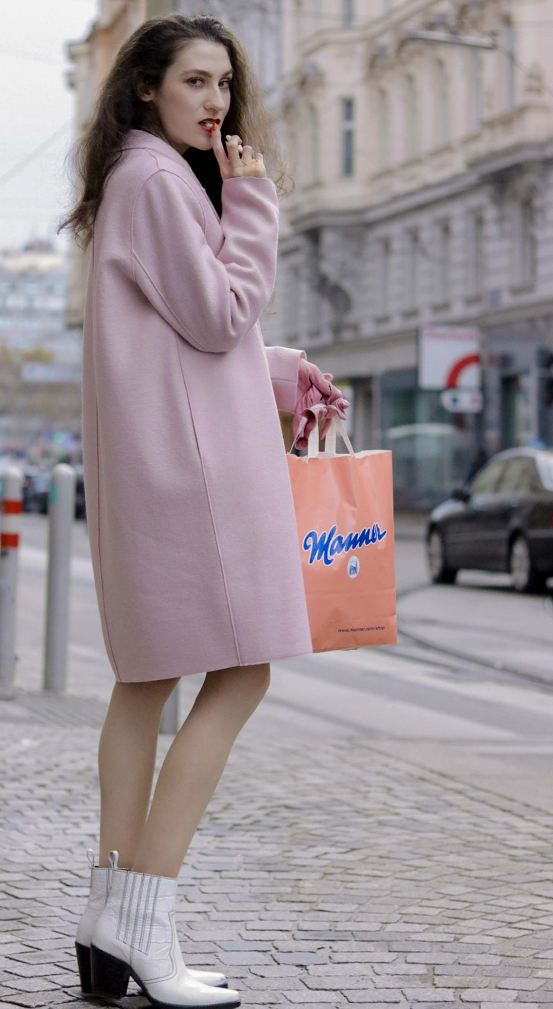 Beautiful Slovenian Fashion Blogger Veronika Lipar of Brunette from Wall wearing Harris Wharf London pink oversized coat, Ganni white cowboy boots, carrying pink Manner shopping bag eating Manner wafers on the street in Wein Austria