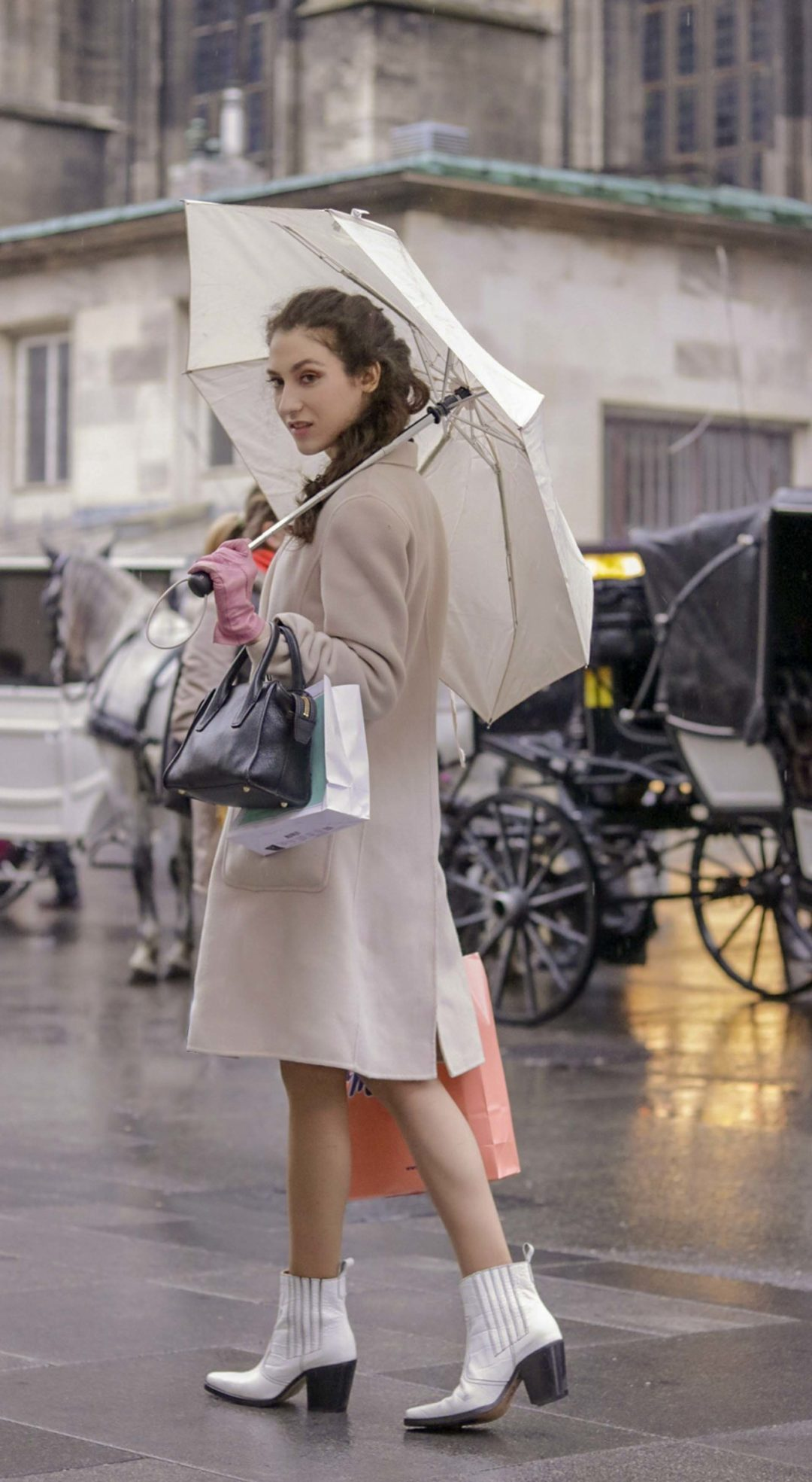 Beautiful Slovenian Fashion Blogger Veronika Lipar of Brunette from Wall wearing Max Mara coat, Ganni white cowboy boots, holding umbrella in rain in Stephansplatz in Wein Austria