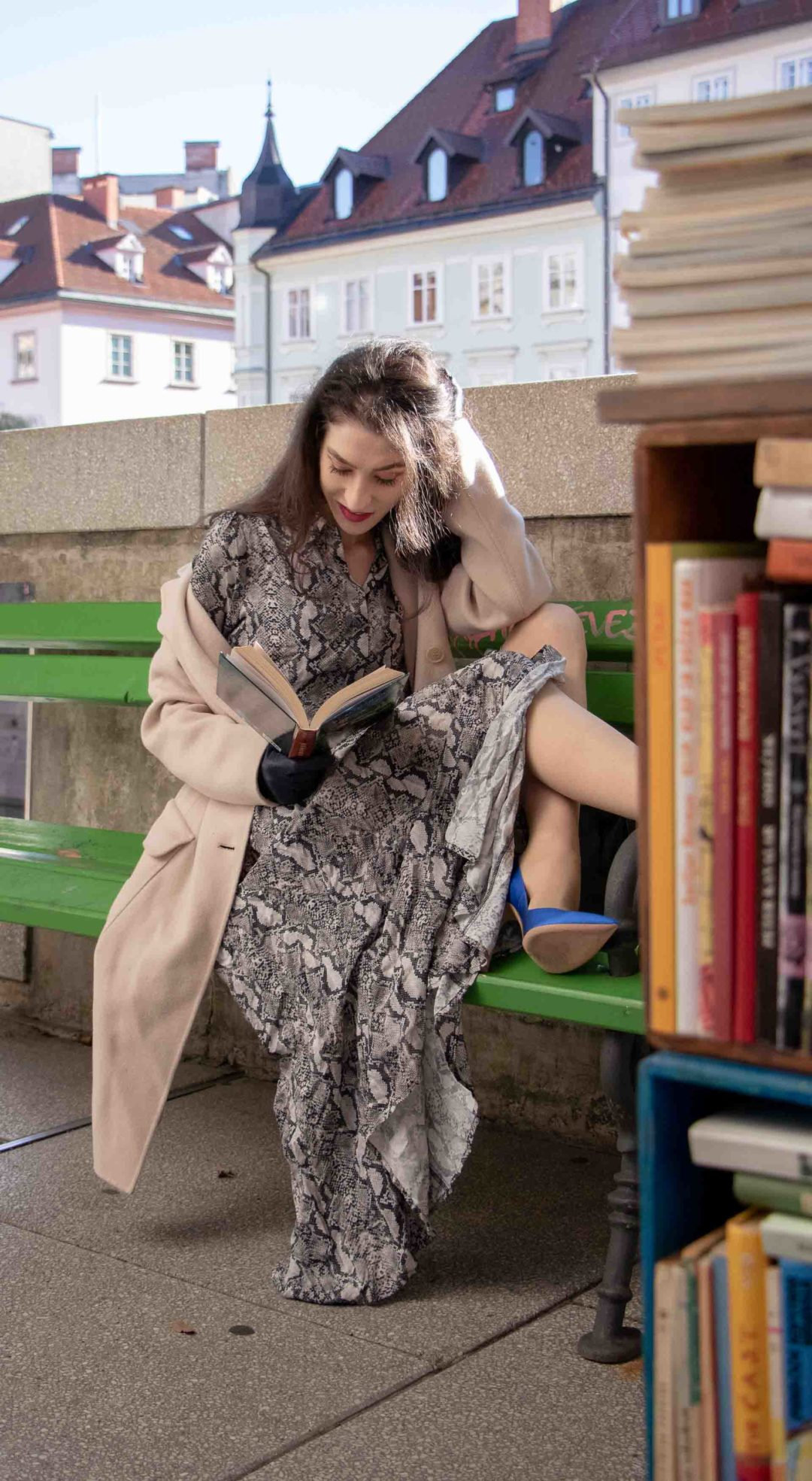 Beautiful Slovenian Fashion Blogger Veronika Lipar of Brunette from Wall dressed in Weekend Max Mara double-breasted coat, snakeskin print long Zara dress, Gianvito Rossi blue satin pumps, blue gloves, black top handle bag sitting on the green bench in Ljubljana reading book