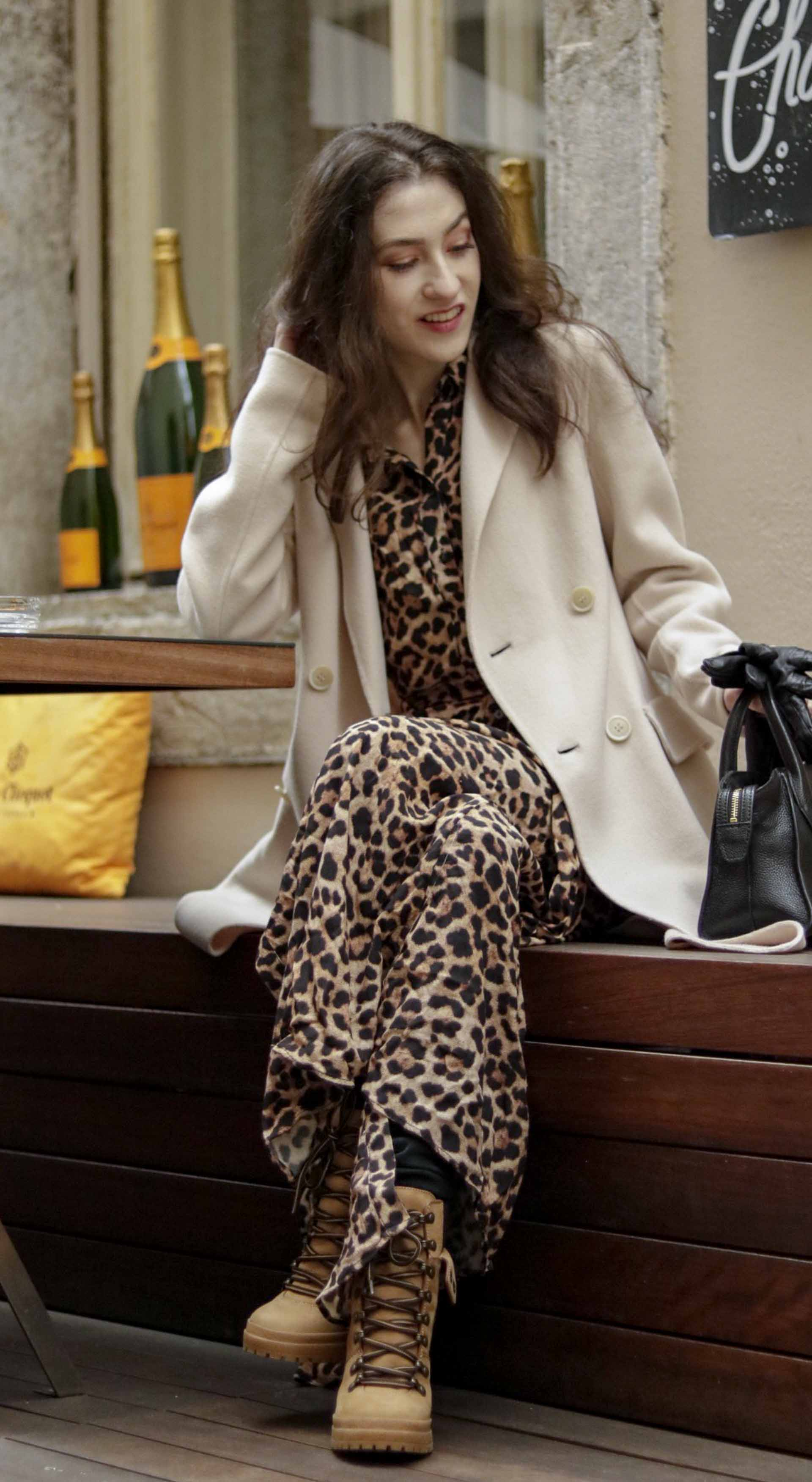 Beautiful Slovenian Fashion Blogger Veronika Lipar of Brunette from Wall wearing Weekend Max Mara double-breasted coat, leopard print long Ganni dress, See By Chloé hiking boots, black skinny jeans for outdoor party in winter