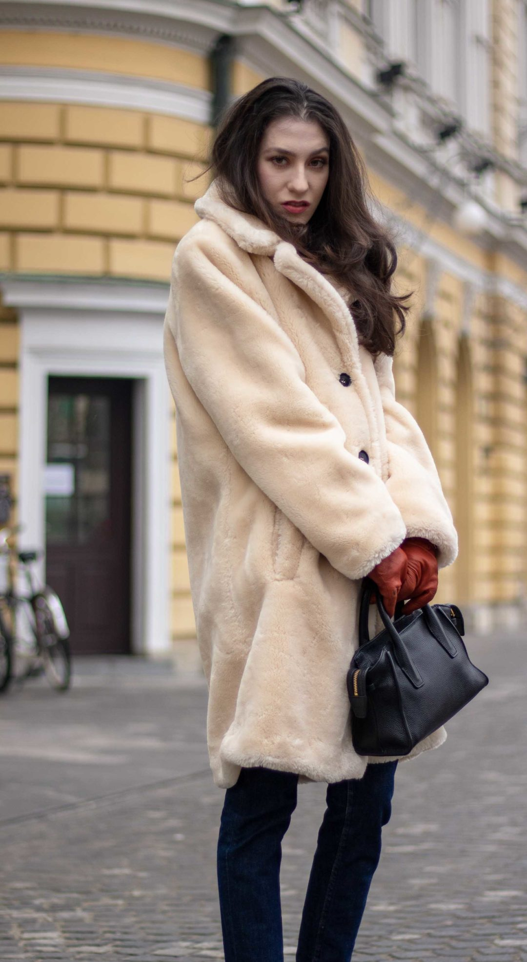 Must follow Slovenian fashion blogger Veronika Lipar of Brunette from Wall Street wearing Mango white teddy bear coat, dark blue A.P.C. denim jeans, black top handle small bag, brown leather gloves in winter on the street
