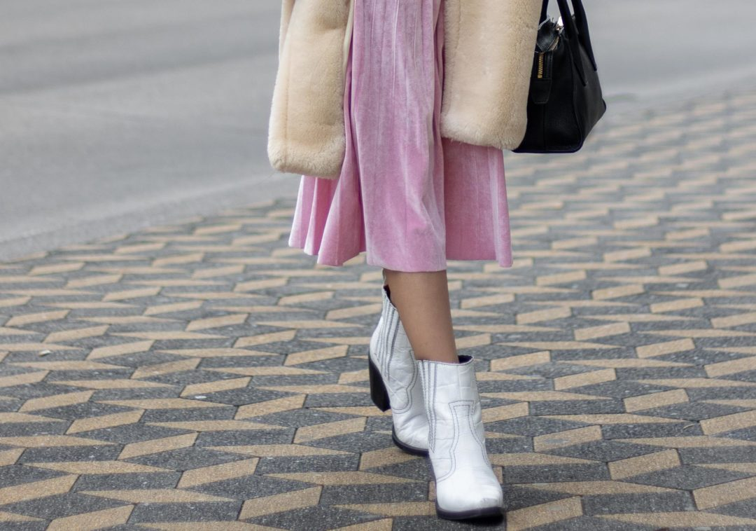 Fashion blogger to follow Veronika Lipar of Brunette from Wall Street dressed in Mango teddy coat, pink midi pleated skirt, white Ganni cowboy boots, black top handle bag, pink gloves in winter walking down the street