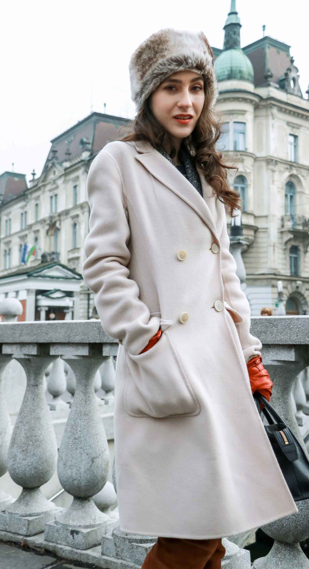 Must follow fashion blogger Veronika Lipar of Brunette from Wall Street dressed in brown Stuart Weitzman OTK boots, fur headband, Weekend Max Mara taupe off white coat, Theory brown suede skirt, brown gloves, holding black handbag