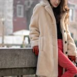Must follow fashion blogger Veronika Lipar of Brunette from Wall Street wearing red skinny jeans, off-white teddy bear coat, black shirt, black top handle bag on the street