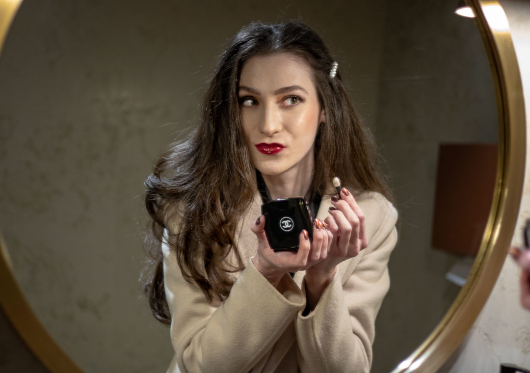 Must follow Fashion Blogger Veronika Lipar of Brunette from Wall Street wearing Max Mara coat, black blazer, pearl hairpin, Chanel Les 4 ombres smokey eye makeup, Tom Ford lip lacquer looking at the mirror getting ready for date night out party