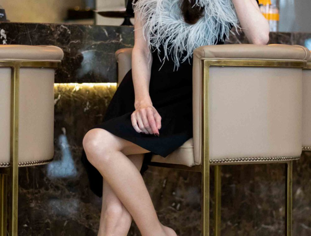 Popular Fashion Blogger Veronika Lipar of Brunette from Wall Street wearing short sleeve little black dress with feathers, rose gold Malone Souliers mules, black top handle bag for party