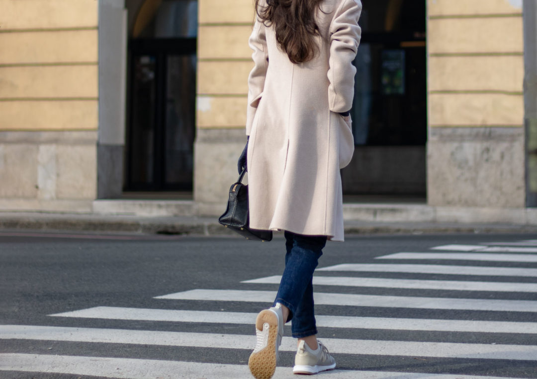 Slovenian Fashion blogger Veronika Lipar of Brunette from Wall Street crossing the street wearing New Balance low sneakers, A.P.C. blue indigo jeans, black silk top, Weekend Max Mara beige coat, black top handle small bag, pearl hairpin