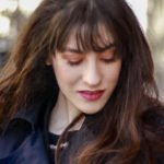 Popular fashion blogger Veronika Lipar of Brunette from Wall Street wearing fringe on long hair, spring makeup, blue trench coat like Parisienne