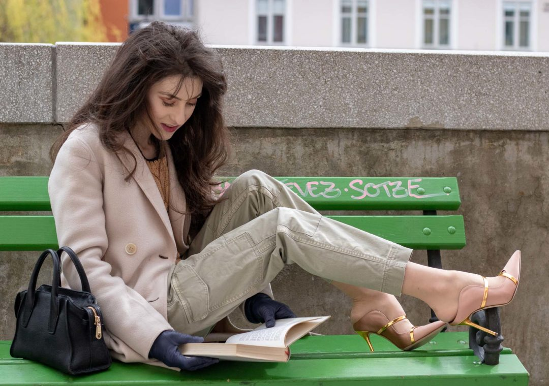 Slovenian fashion blogger & entrepreneur Veronika Lipar of Brunette from Wall Street wearing khaki cargo pants beige cable knit Mango sweater off-white Weekend Max Mara coat pink and gold Malone Souliers mules blue leather gloves black small bag reading a book on a bench