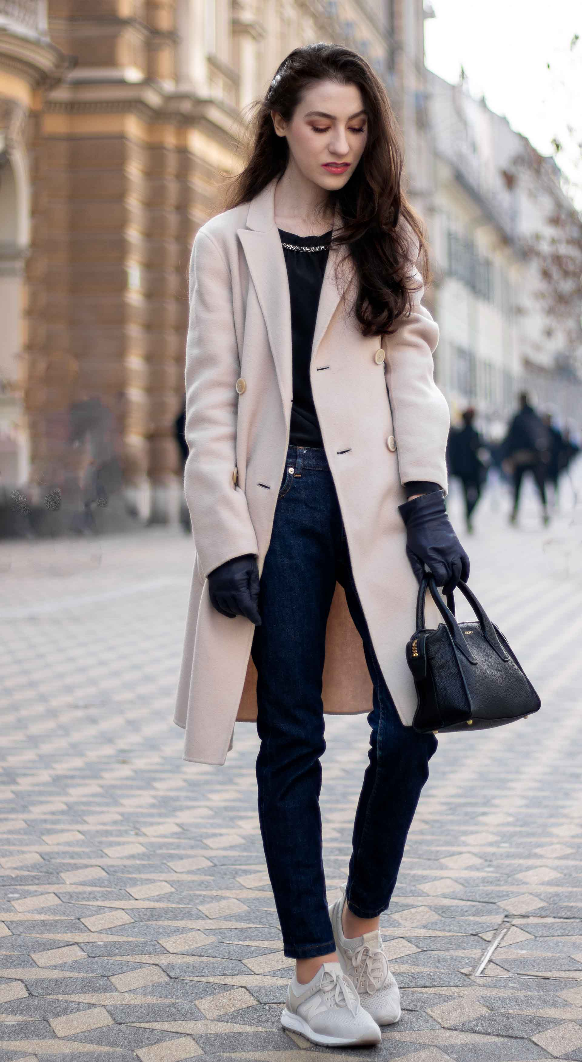 Best street fashion blogger Veronika Lipar of Brunette from Wall Street standing on the street wearing white grey New Balance sneakers blue leather gloves black small top handle bag black blouse dark blue jeans Weekend Max Mara double-breasted coat pearl hairpin