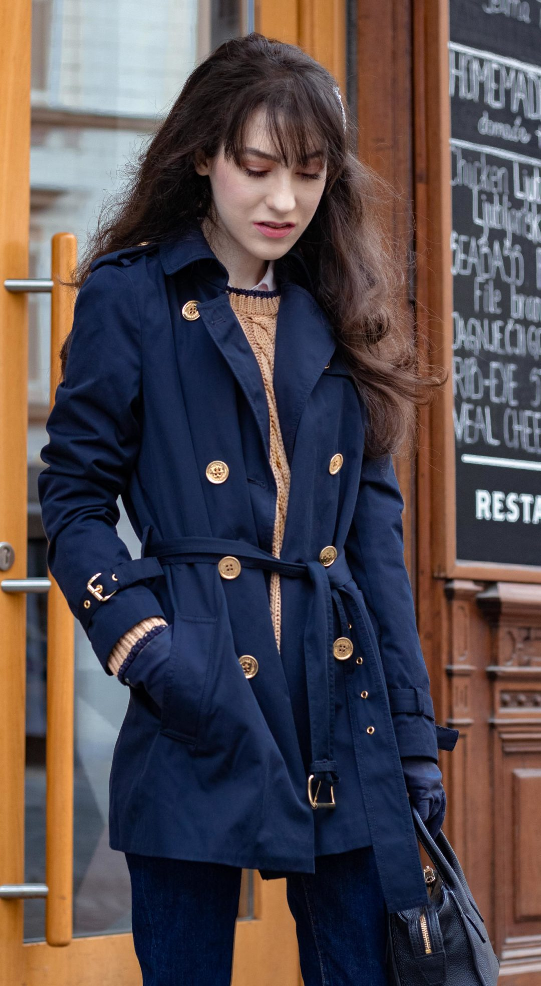 Must follow fashion blogger Veronika Lipar of Brunette from Wall Street dressed in Micael Kors blue trench coat Mango camel cable knit sweater A.P.C. denim jeans Forzieri small top handle black bag blue leather gloves fringe bangs on long hair pearl hairpin on the street