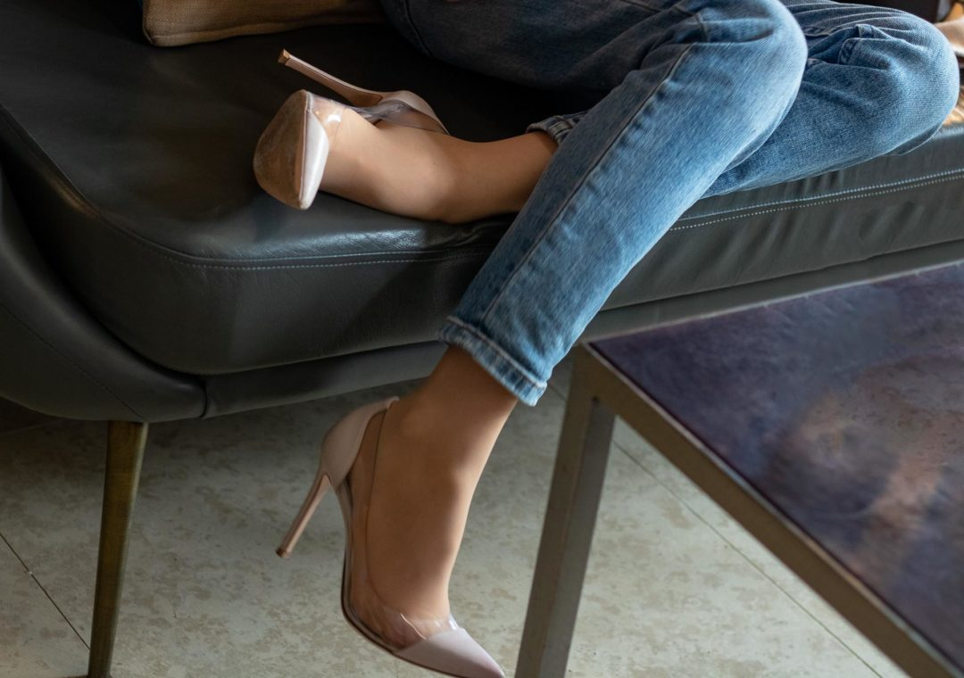 Brunette from Wall Street plexi pumps washed denim jeans sitting on sofa