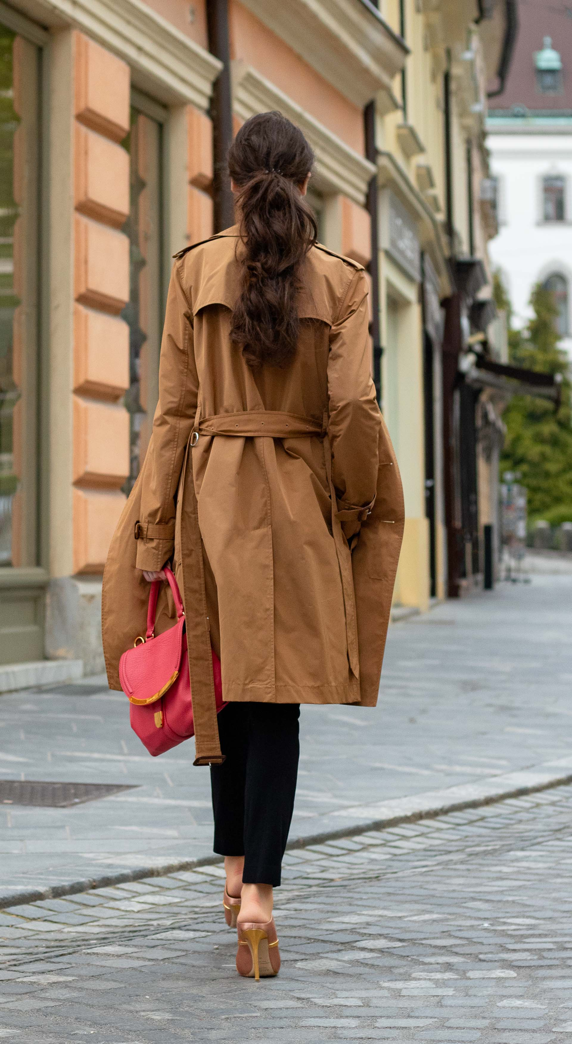 Must follow Slovenian Fashion Blogger Veronika Lipar of Brunette from Wall Street wearing camel Burberry trench coat black trousers blush Malone Souliers mules pink top handle bag low ponytail bangs going to the office