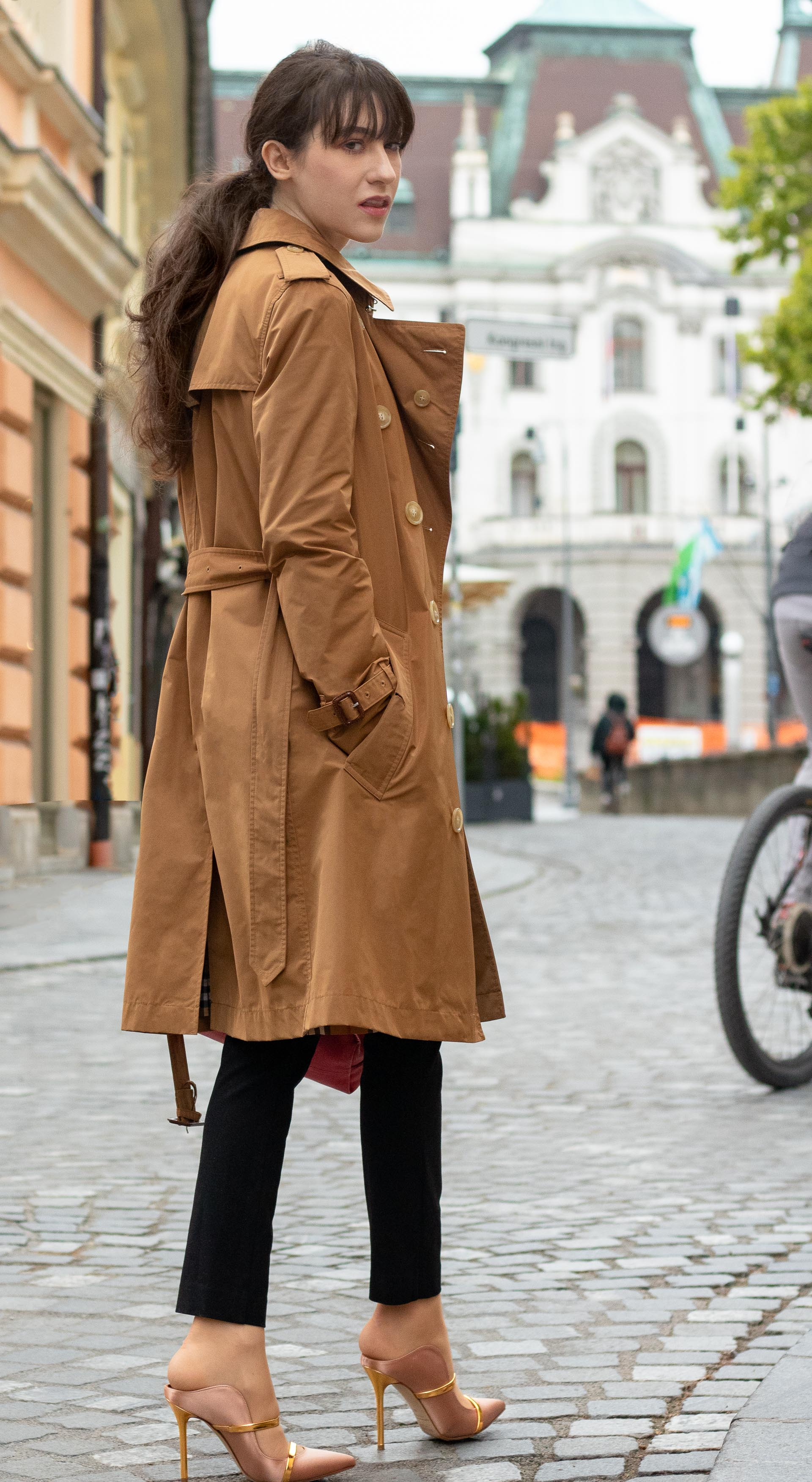 Must follow Slovenian Fashion Blogger Veronika Lipar of Brunette from Wall Street wearing camel Burberry trench coat black trousers blush Malone Souliers mules pink top handle bag low ponytail bangs going to work