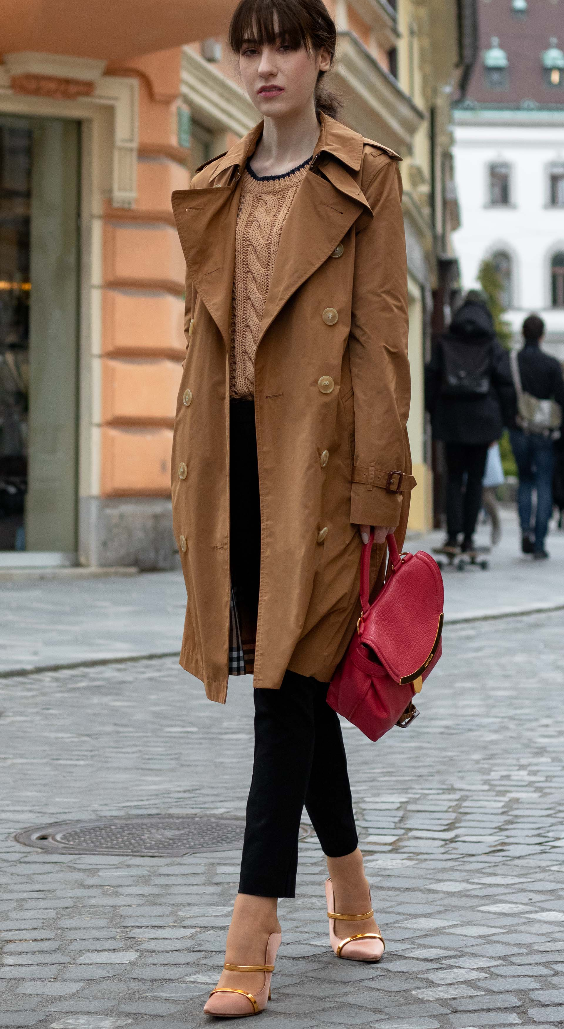 Must follow Slovenian Fashion Blogger Veronika Lipar of Brunette from Wall Street dressed in camel Burberry trench coat Mango cable knit sweater black trousers blush Malone Souliers mules pink top handle bag low ponytail bangs going to work