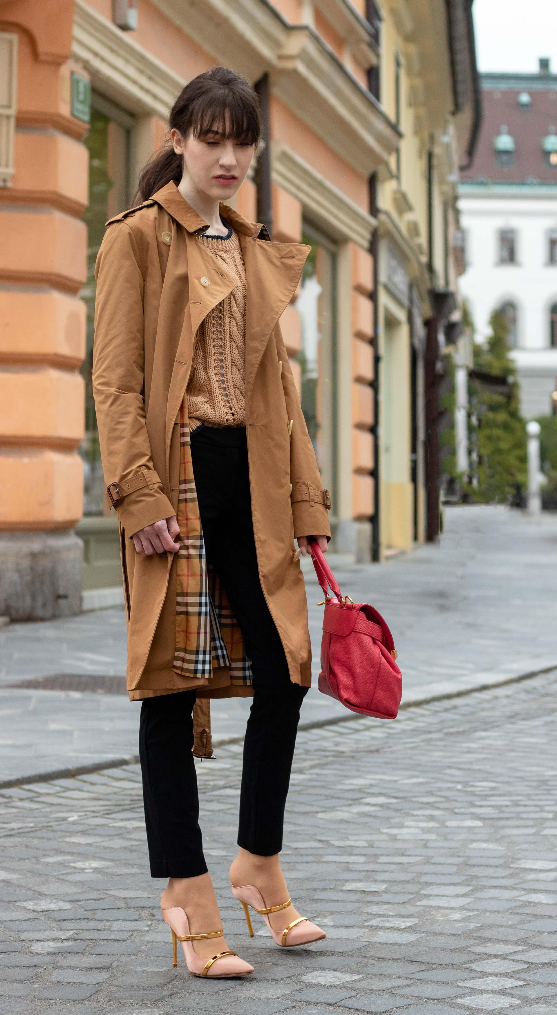 Must follow Slovenian Fashion Blogger Veronika Lipar of Brunette from Wall Street wearing camel Burberry trench coat Mango cable knit sweater black trousers blush Malone Souliers mules pink top handle bag low ponytail bangs going to work