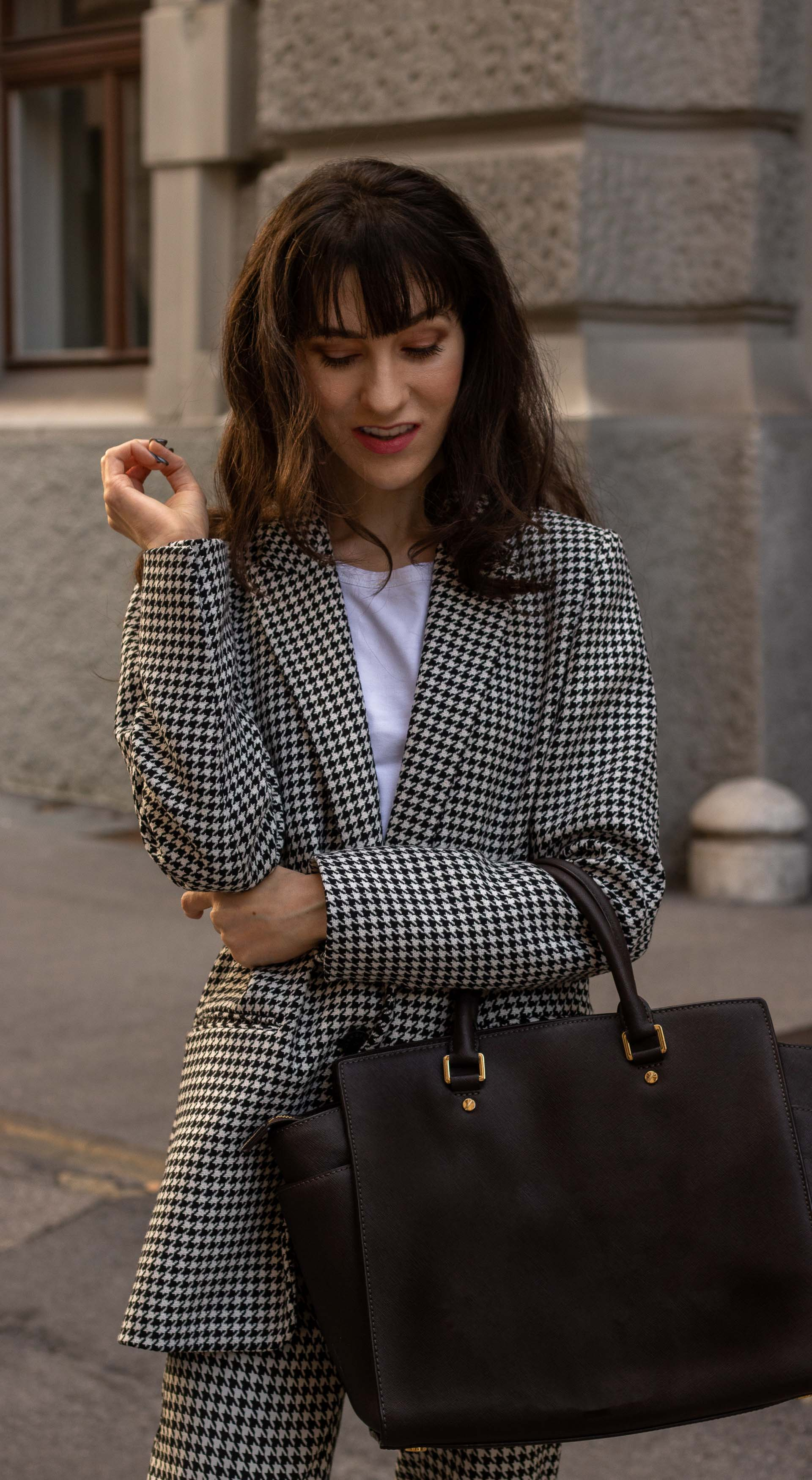 Fashion blogger Veronika Lipar of Brunette from Wall Street dressed in Sandro Paris houndstooth suit Mihael Kors brown tote bag