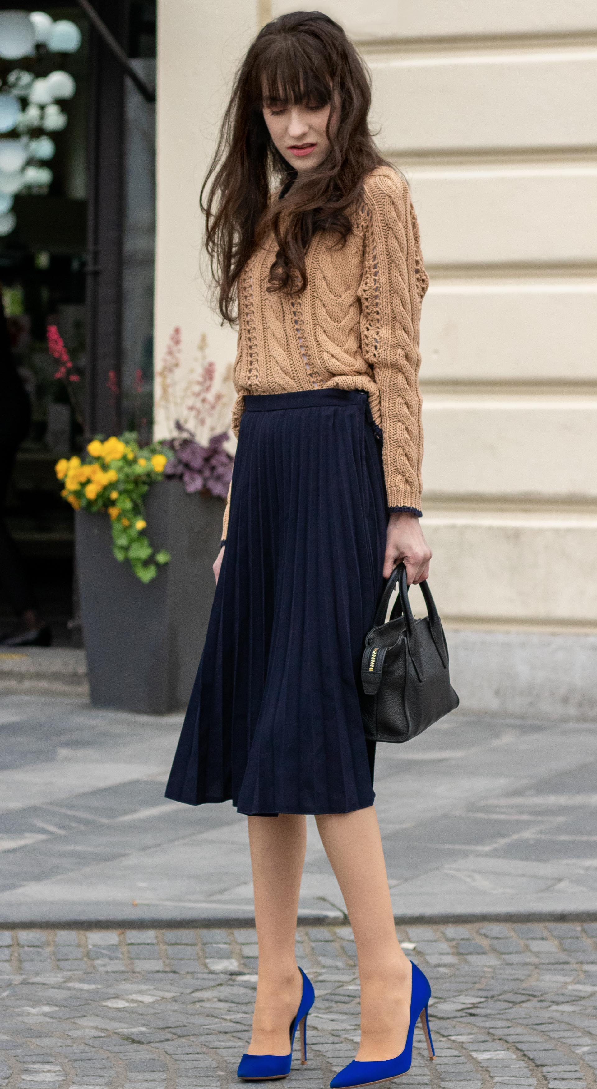 Must follow fashion blogger Veronika Lipar of Brunette from Wall Street dressed in camel beige Mango cable knit camel sweater blue pleated midi skirt blue Gianvito Rossi pumps black top handle bag bangs on long hair standing on the street