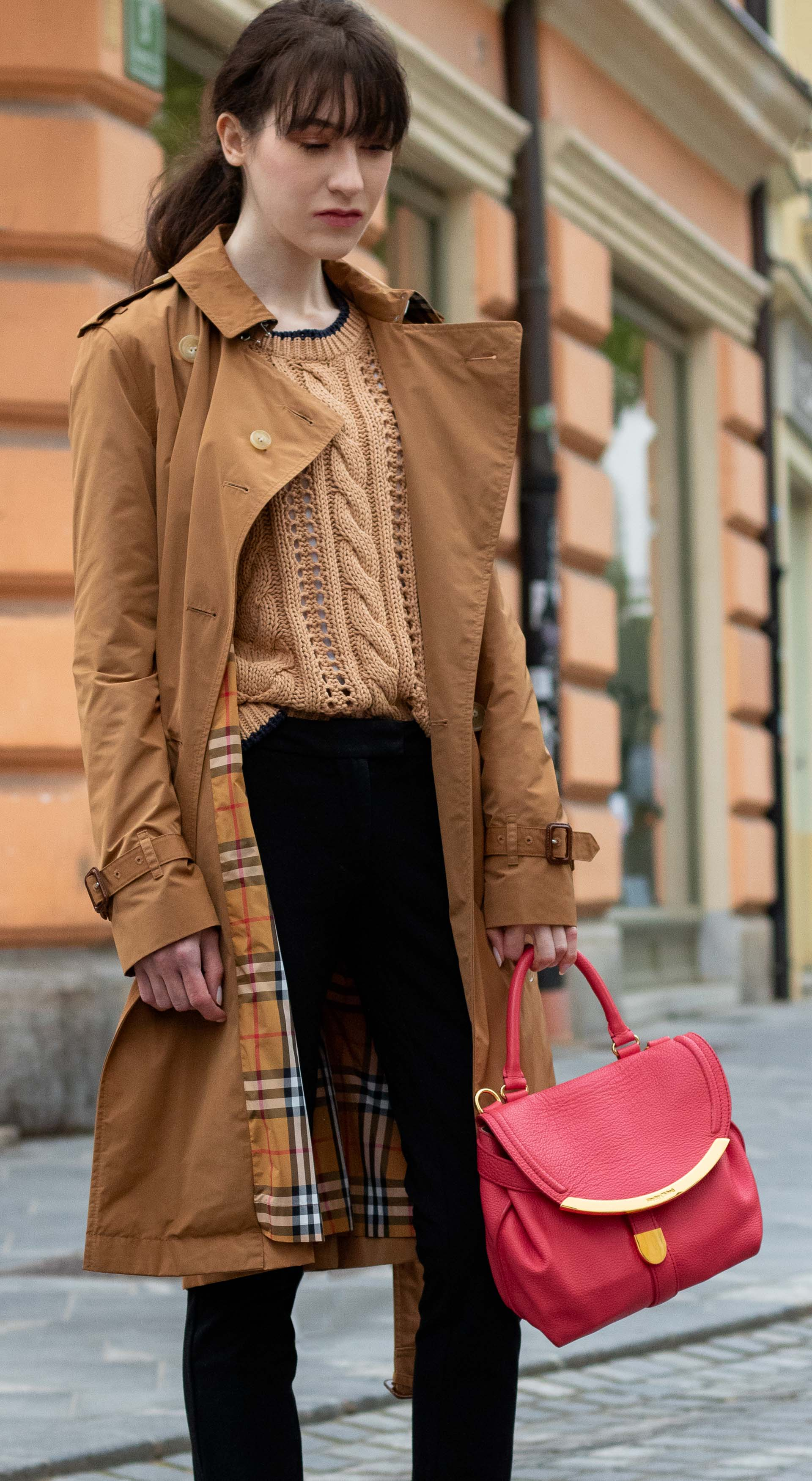 Must follow Slovenian Fashion Blogger Veronika Lipar of Brunette from Wall Street wearing camel Burberry trench coat Mango cable knit sweater black trousers pink top handle bag low ponytail bangs going to work