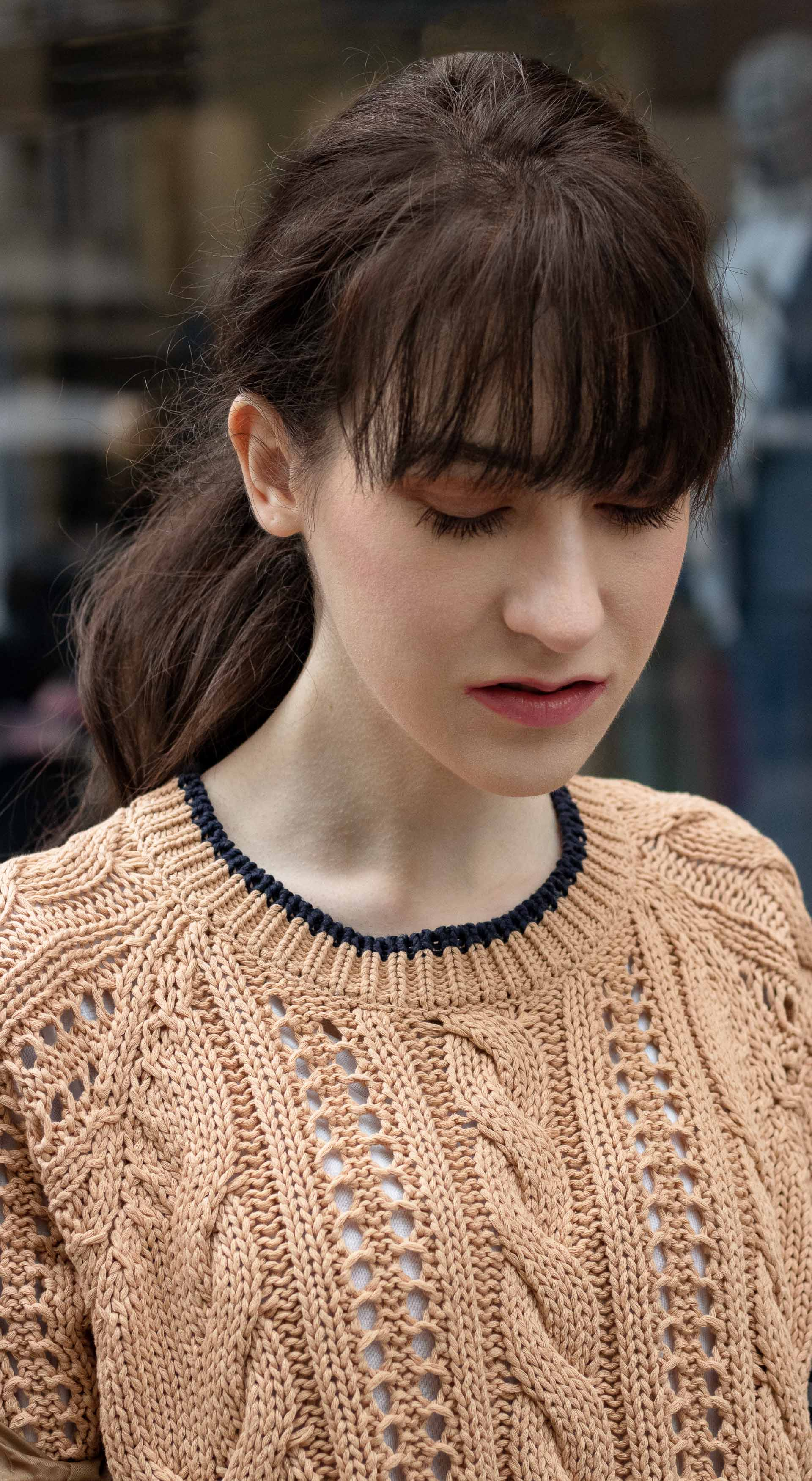 Veronika Lipar Brunette from Wall Street camel beige sweater low ponytail bangs beige makeup