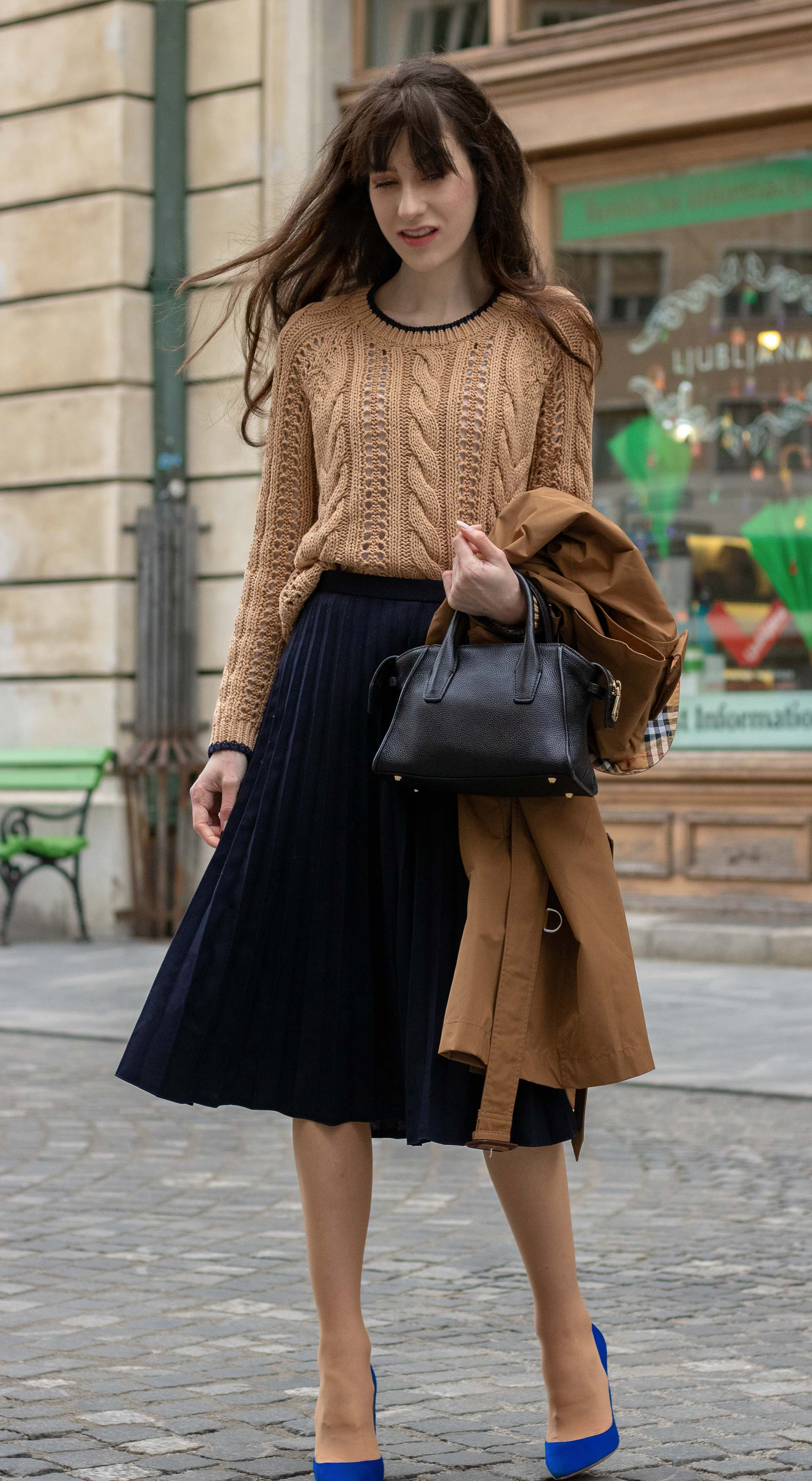 Must follow fashion blogger Veronika Lipar of Brunette from Wall Street wearing Mango cable knit camel sweater blue pleated midi skirt blue Gianvito Rossi pumps black top handle bag bangs on long hair holding camel beige Burberry Kensington trench coat in her hand standing on the street