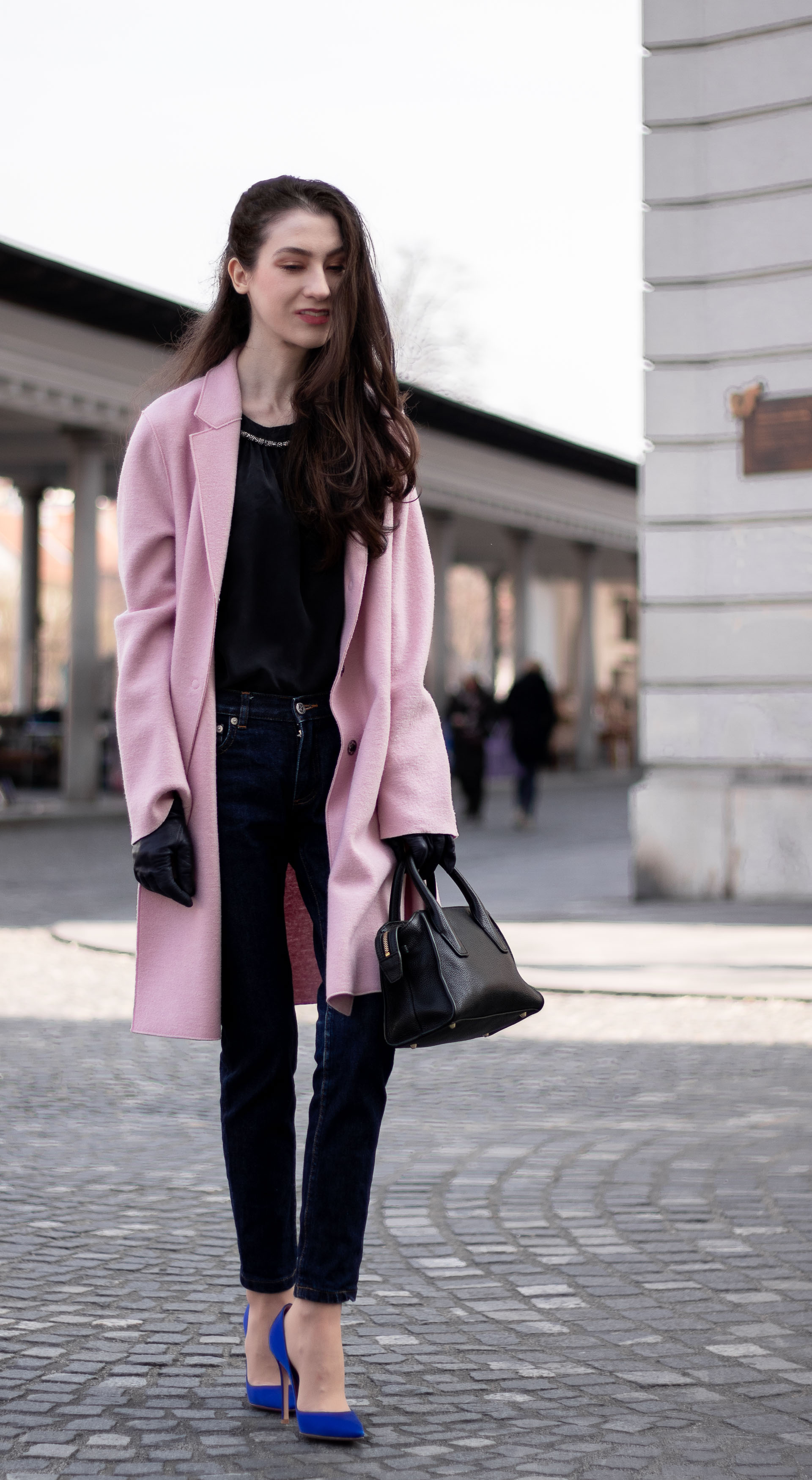Must follow Fashion Blogger Veronika Lipar of Brunette from Wall Street wearing loose pink Harris Wharf London coat A.P.C. Paris dark blue denim jeans Gianvito Rossi blue court shoes black top handle bag Forzieri blue leather gloves pearl hairpin standing on the street