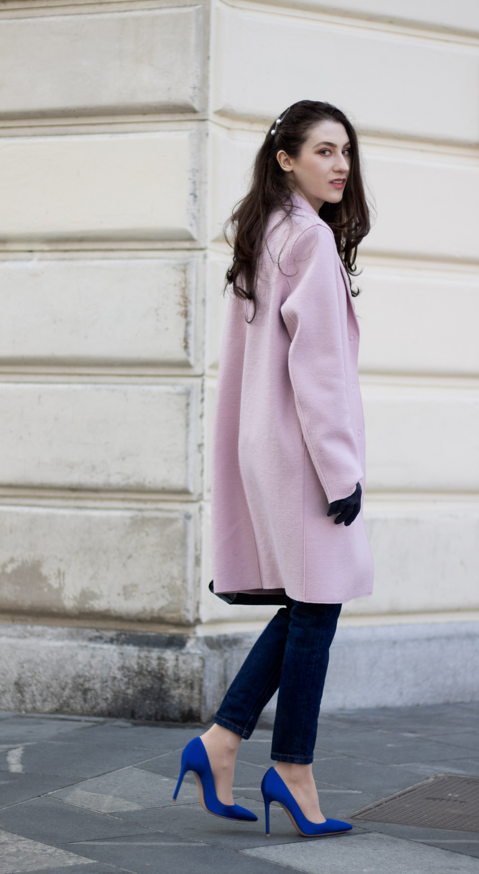 Must follow Fashion Blogger Veronika Lipar of Brunette from Wall Street dressed in oversize pink Harris Wharf London coat A.P.C. Paris dark blue denim jeans Gianvito Rossi blue heels black top handle bag Forzieri blue leather gloves pearl hairpin walking down the street