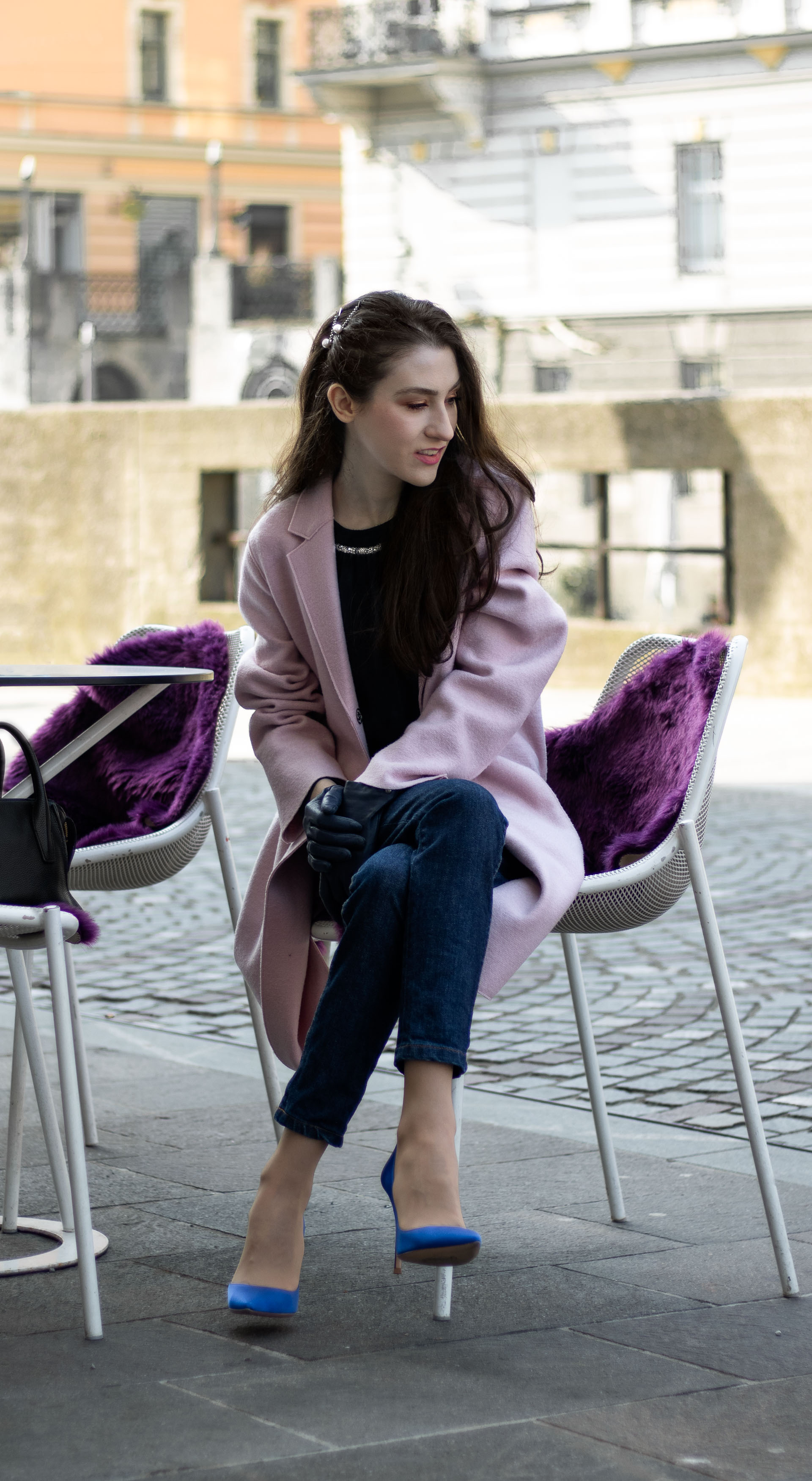 Must follow Fashion Blogger Veronika Lipar of Brunette from Wall Street wearing loose pink Harris Wharf London coat A.P.C. Paris dark blue denim jeans Gianvito Rossi blue pumps black top handle bag Forzieri blue leather gloves pearl hairpin sitting at the table on the street