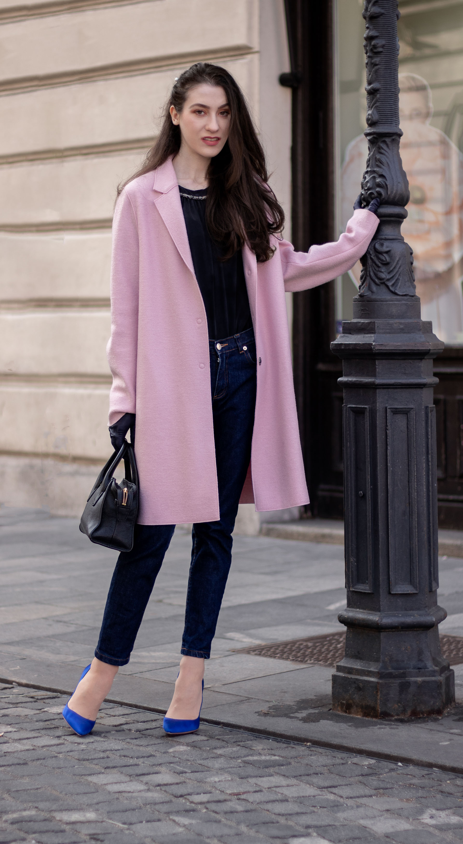 Must follow Fashion Blogger Veronika Lipar of Brunette from Wall Street dressed in oversize pink Harris Wharf London coat A.P.C. Paris dark blue denim jeans black top handle bag Forzieri blue leather gloves pearl hairpin leaning on the street lamp