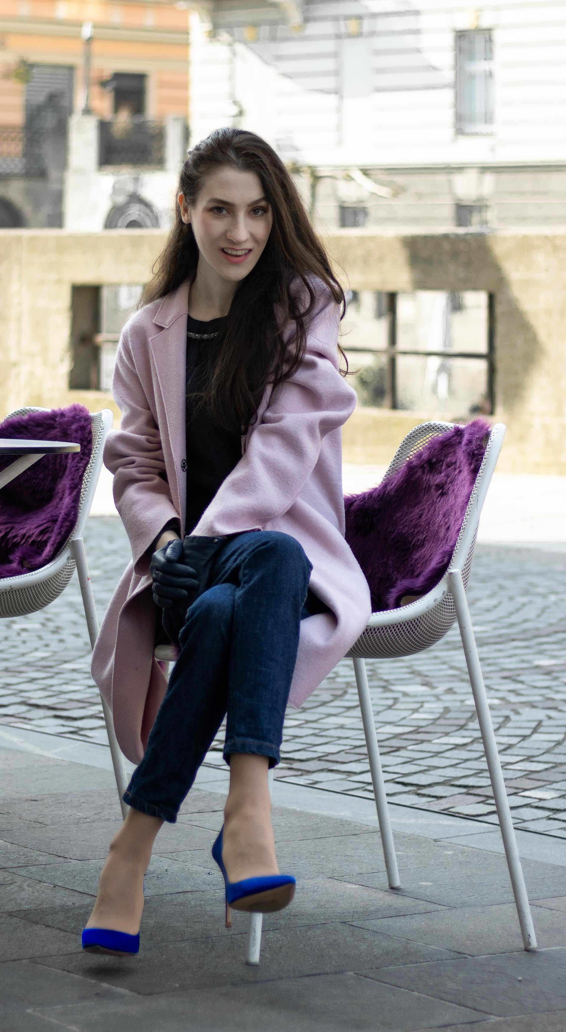 Must follow Fashion Blogger Veronika Lipar of Brunette from Wall Street wearing oversize pink Harris Wharf London coat A.P.C. Paris dark blue denim jeans Gianvito Rossi blue court shoes black top handle bag Forzieri blue leather gloves pearl hairpin sitting