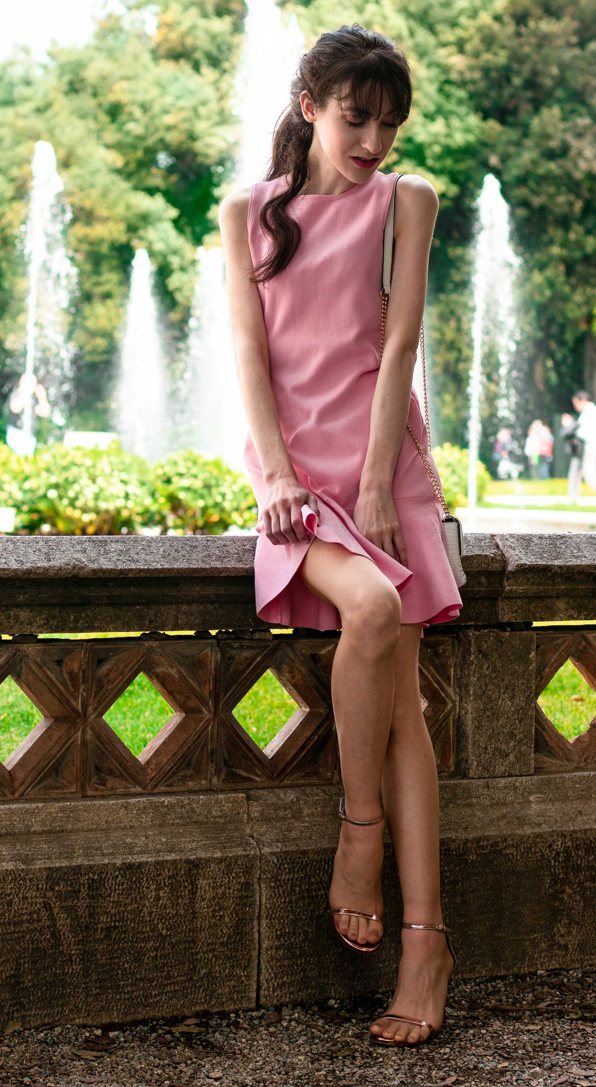 Beautiful Slovenian Fashion Blogger Veronika Lipar of Brunette from Wall Street dressed in super down jazzie ruffle mini pink dress Stuart Weitzman rose gold nudistsong sandals white chain strap shoulder bag low ponytail with bangs for garden wedding