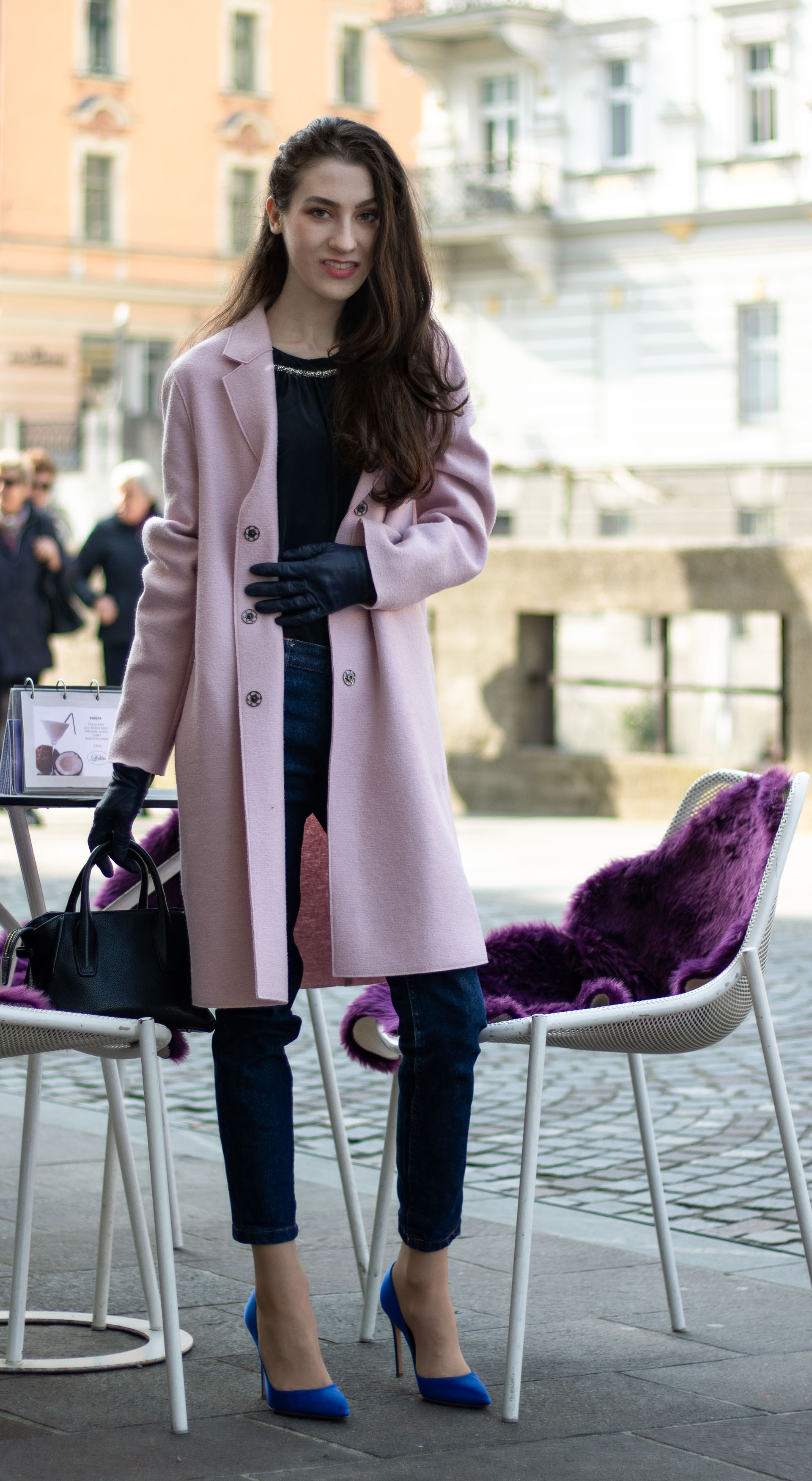 Must follow Fashion Blogger Veronika Lipar of Brunette from Wall Street wearing oversize pink Harris Wharf London coat A.P.C. Paris dark blue denim jeans Gianvito Rossi blue heels black top handle bag Forzieri blue leather gloves pearl hairpin standing by the table on the street